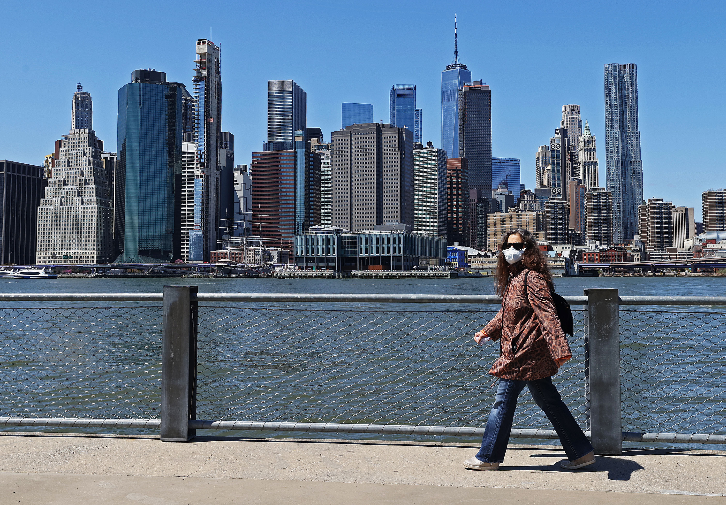 A woman wearing a face mask walks in Brooklyn Bridge Park on April 28 in New York City.