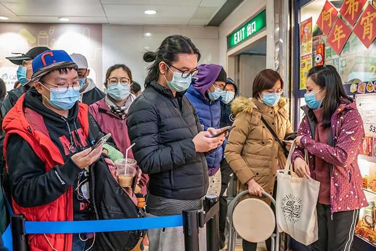 People wait in line to purchase surgical masks in a  Hong Kong shopping mall on January 29.