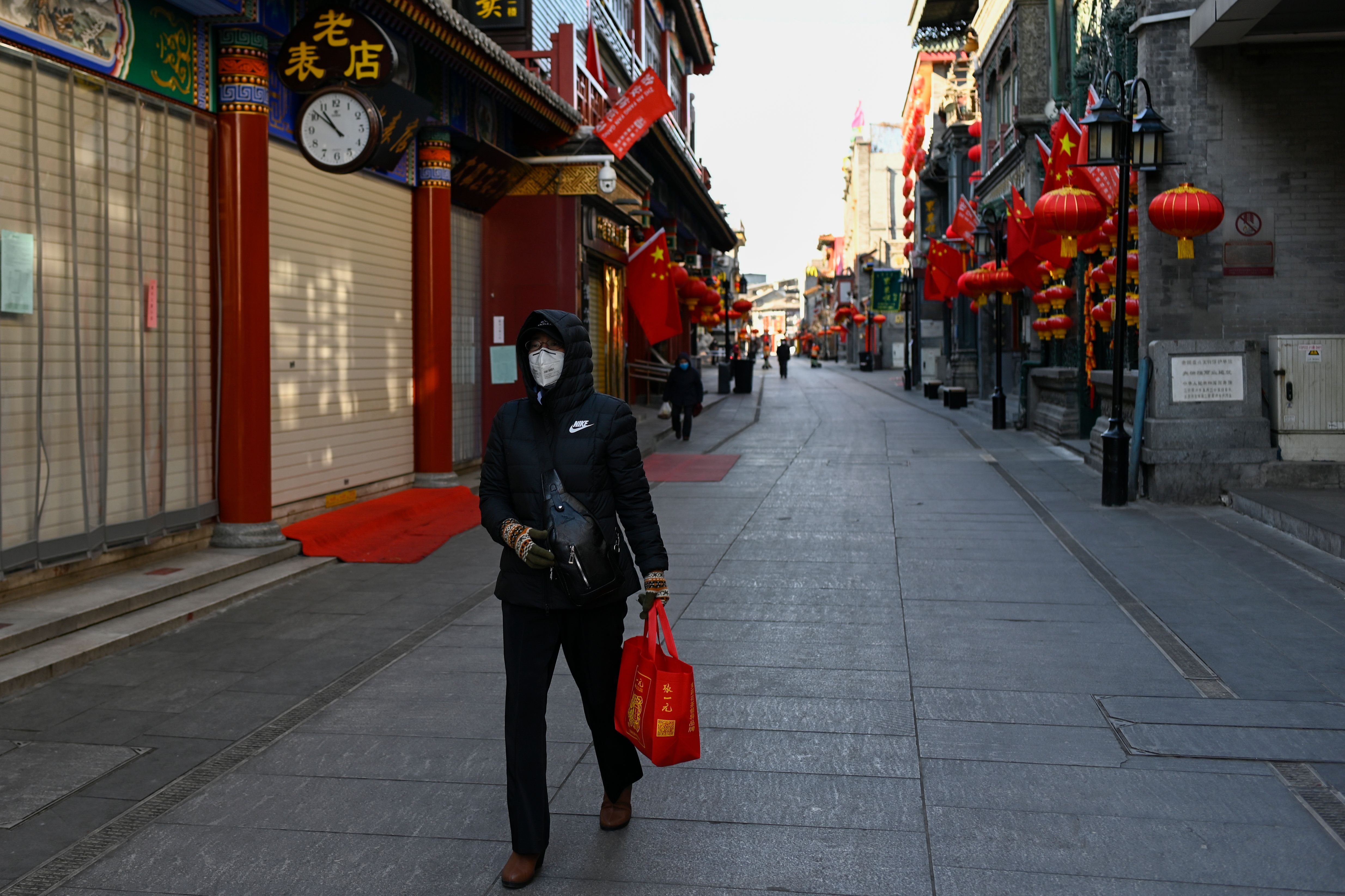 A woman walks past closed shops and businesses in Beijing on February 4, 2020.