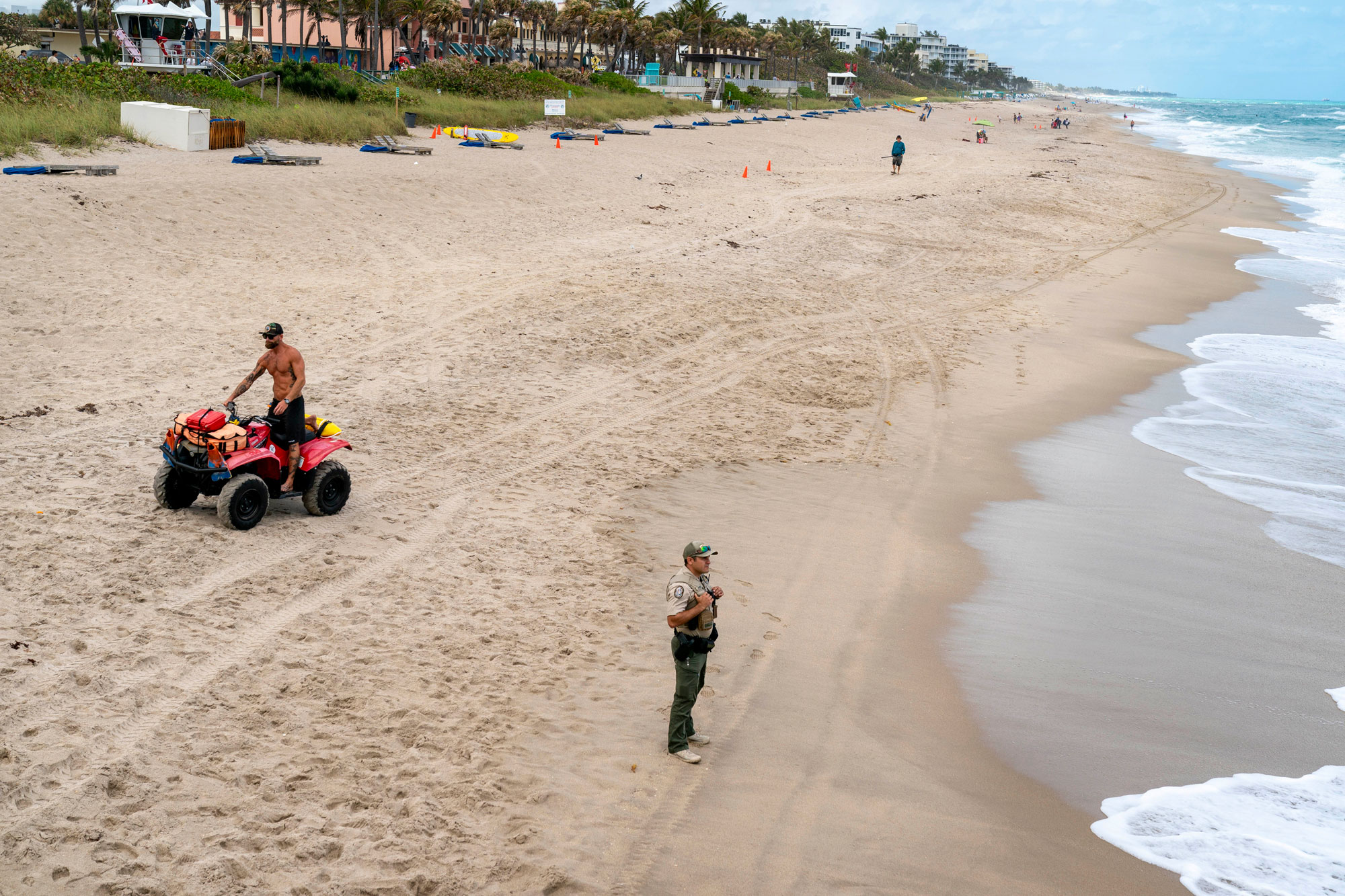 Lake Worth Beach lifeguard captain Michael Tricarico, left and FWC officer Ryan Ames clear the beach on March 20 in Lake Worth, Florida.