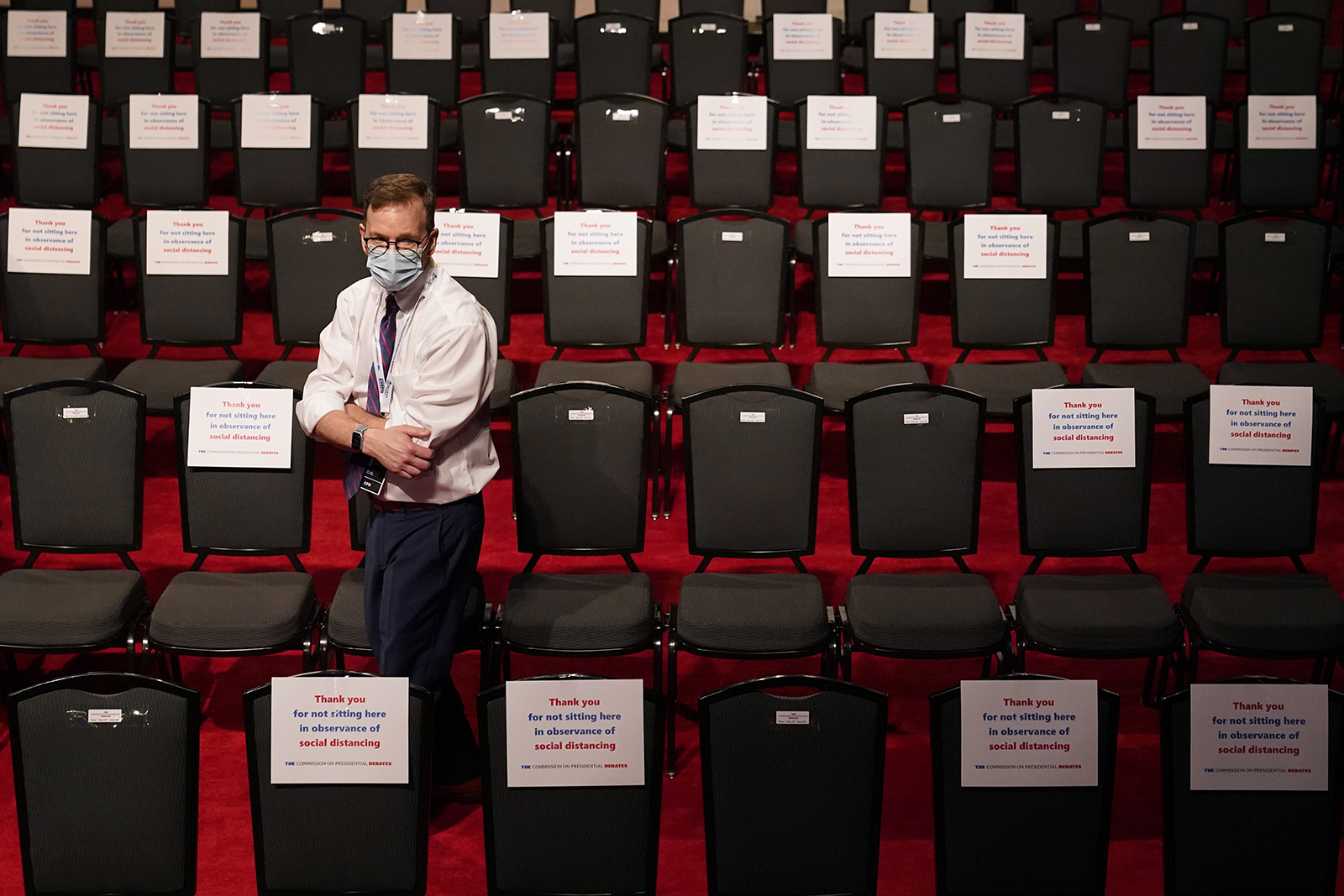 A debate official walks past spectator seating marked with signs observing social distancing requirements for the final debate between President Donald Trump and Democratic presidential candidate Joe Biden at Belmont University on Thursday.