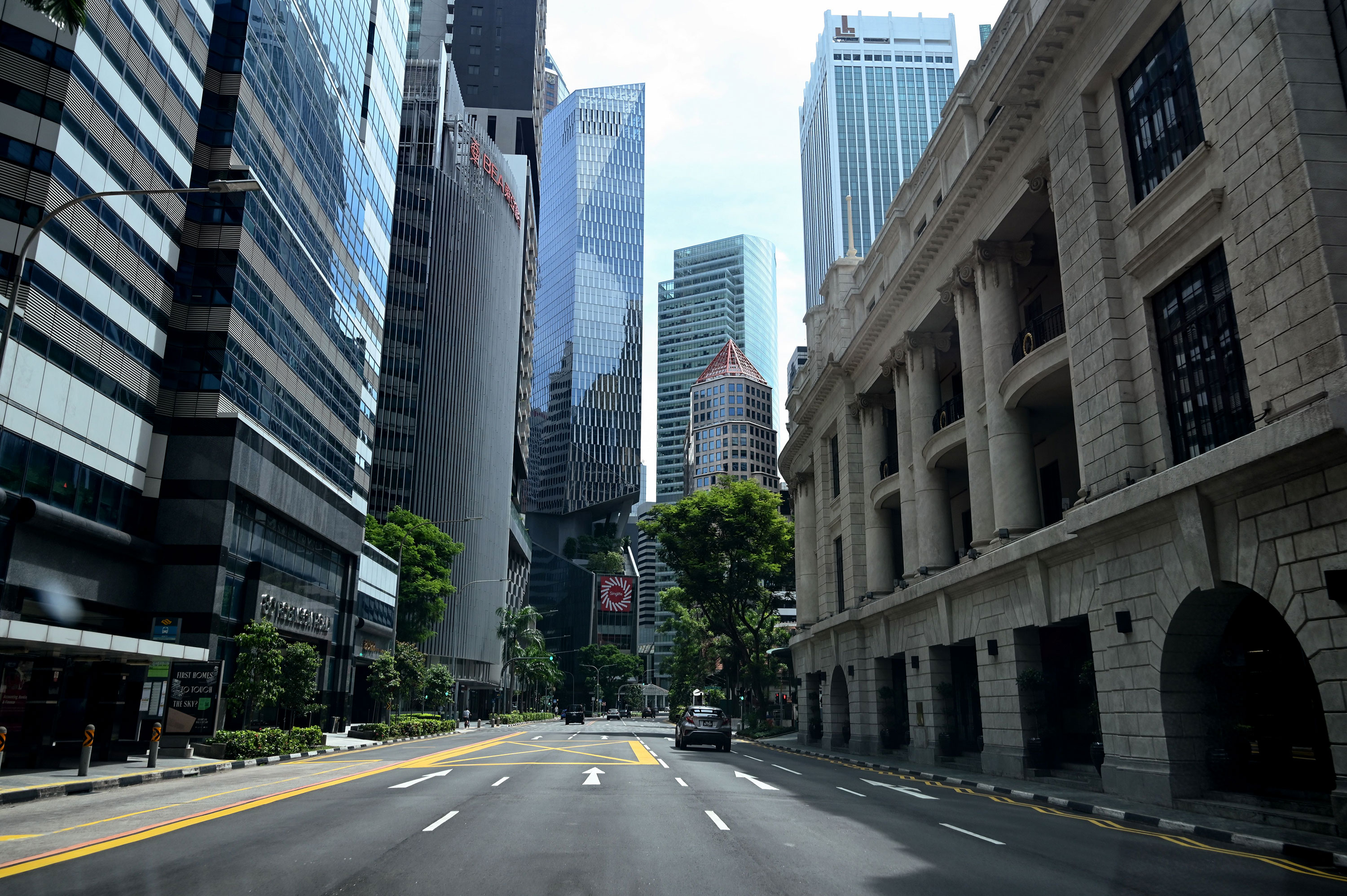 A car drives along an otherwise empty road in Singapore's financial district on April 24.