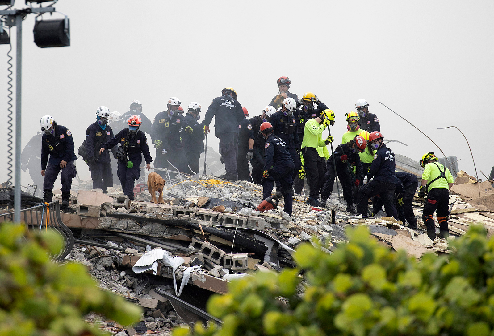 Members of the South Florida Urban Search and Rescue team look for possible survivors in the partially collapsed 12-story Champlain Towers South condo building on June 25, in Surfside, Florida.