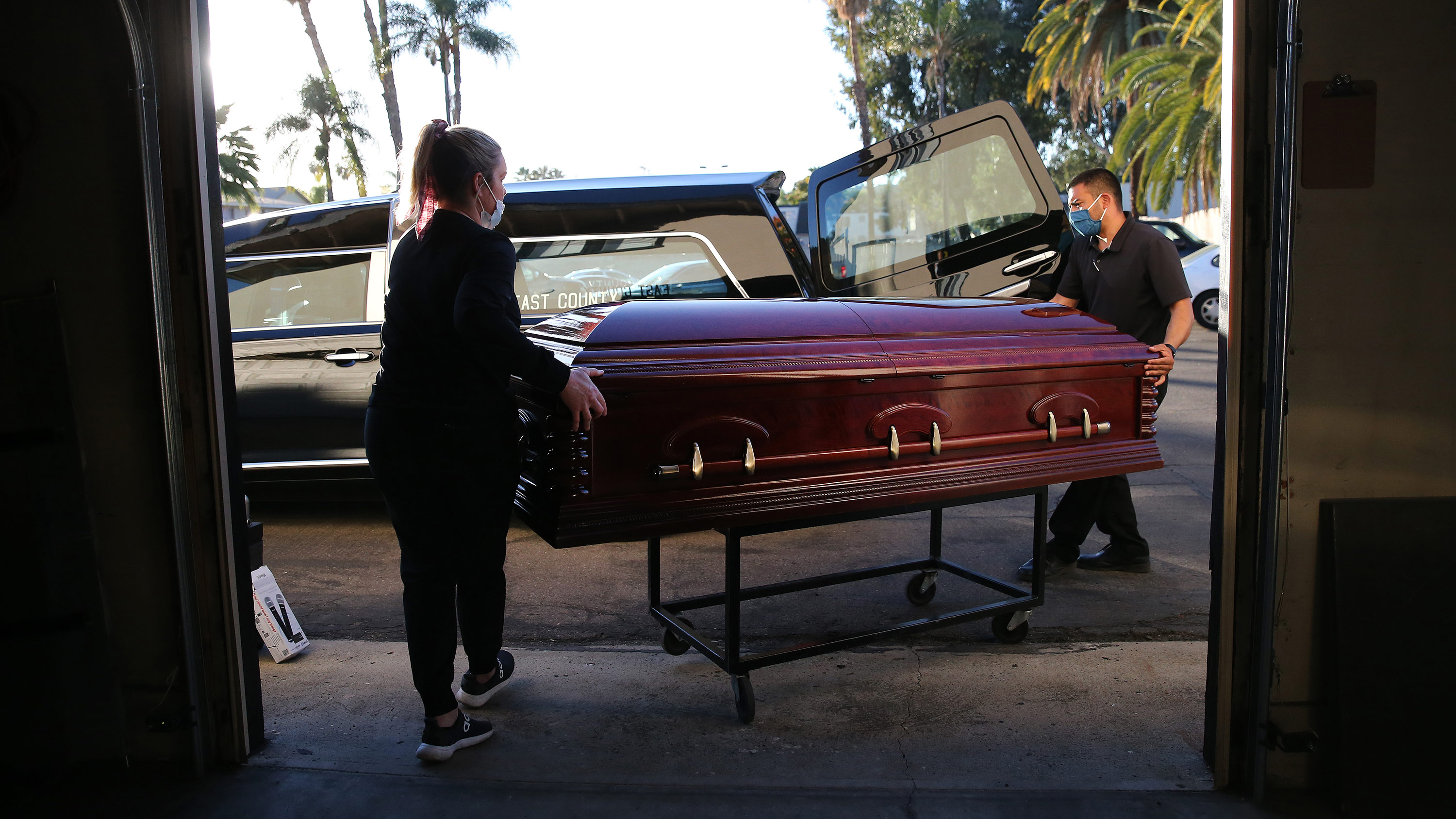 Funeral workers load the casket of a Covid-19 victim into a hearse at East County Mortuary on January 15, in El Cajon, California.