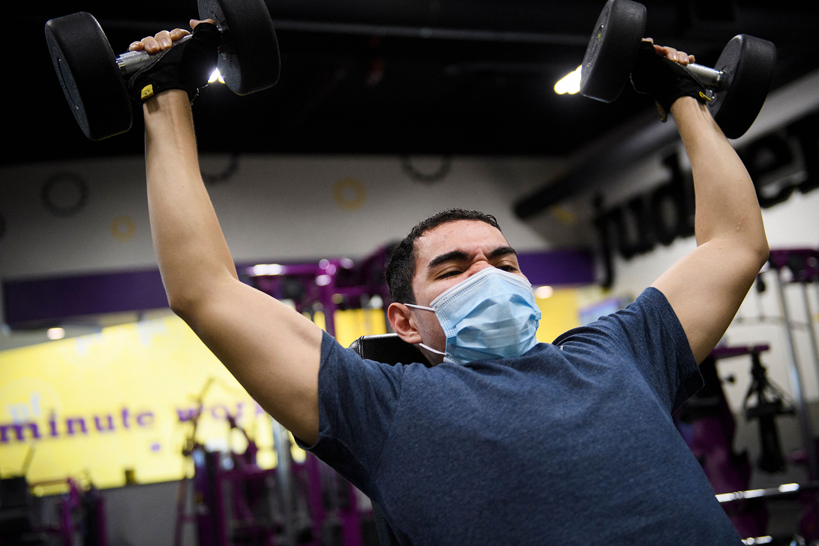 A customer wears a face mask as they lift weights inside a Planet Fitness Inc. gym on March 16, in Inglewood, California.
