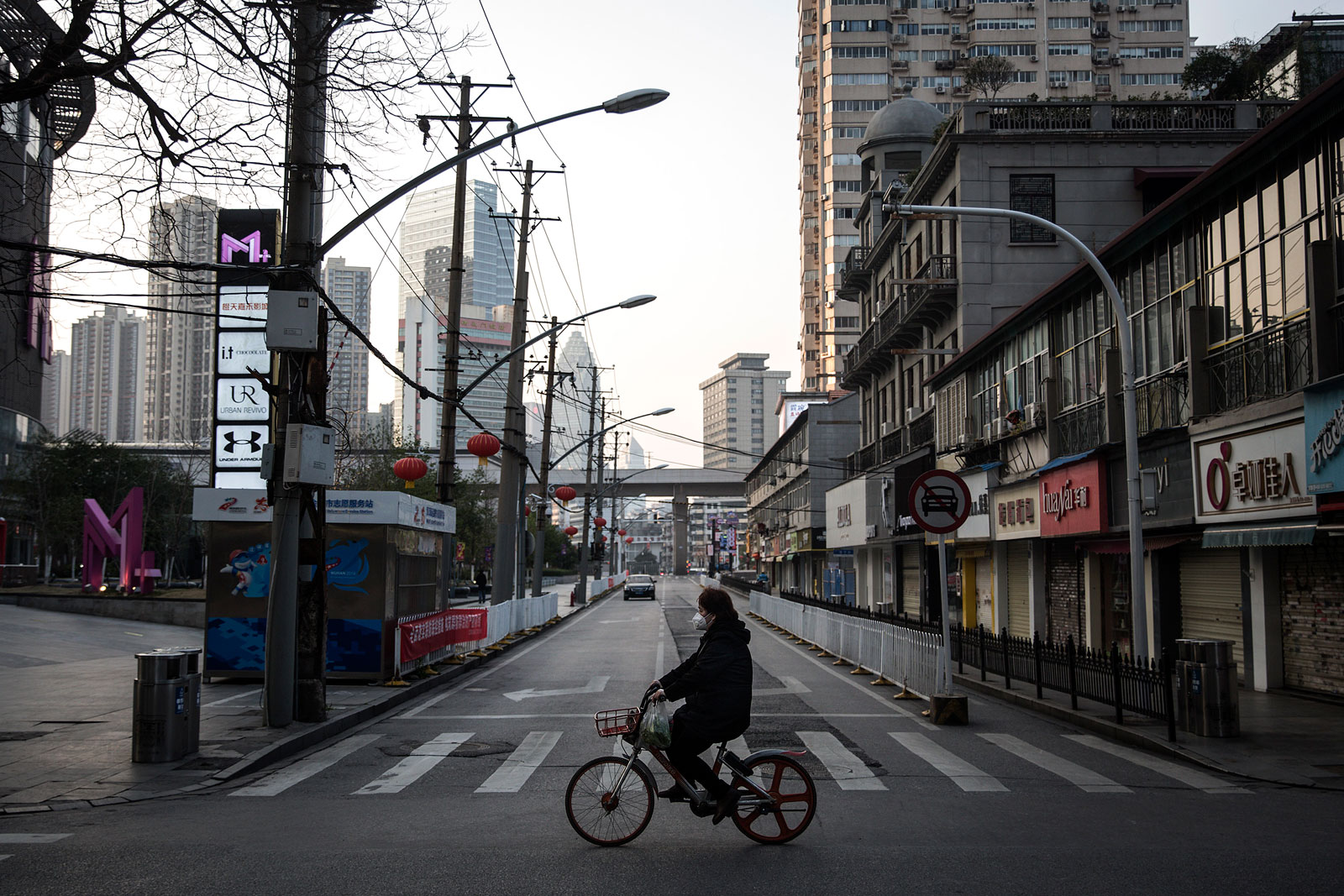 A women wears a protective mask as she ride a bicycle in the empty business street on February 13 in Wuhan, China.