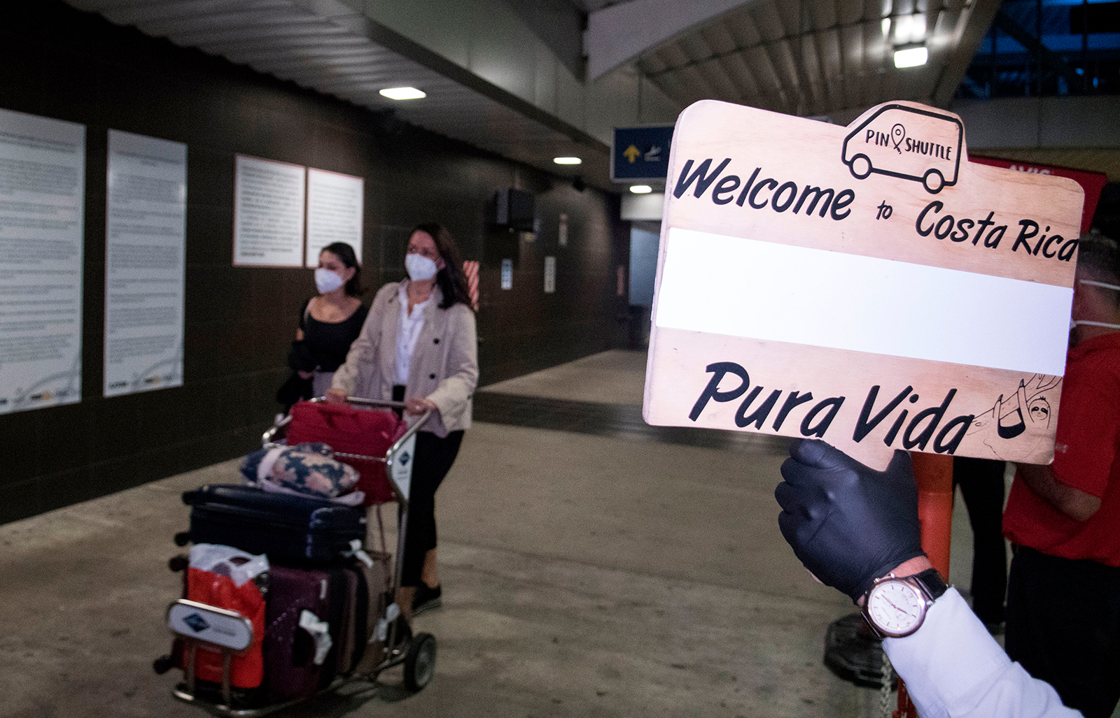 "People arrive at Juan Santamaria airport where they are greeted by a tour operator with a sign saying ""Welcome to Costa Rica, Pura Vida"" in San Jose, on August 3."
