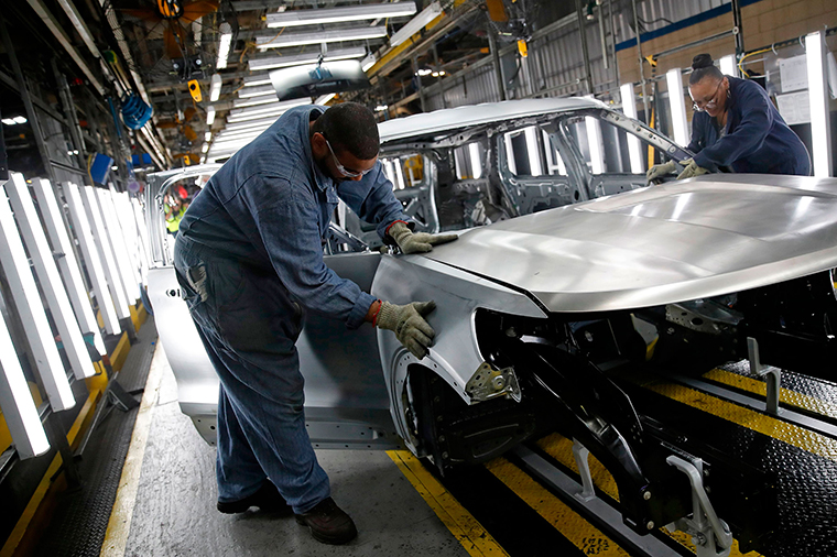 Workers assemble cars at the newly renovated Ford's Assembly Plant in Chicago, June 24, 2019.