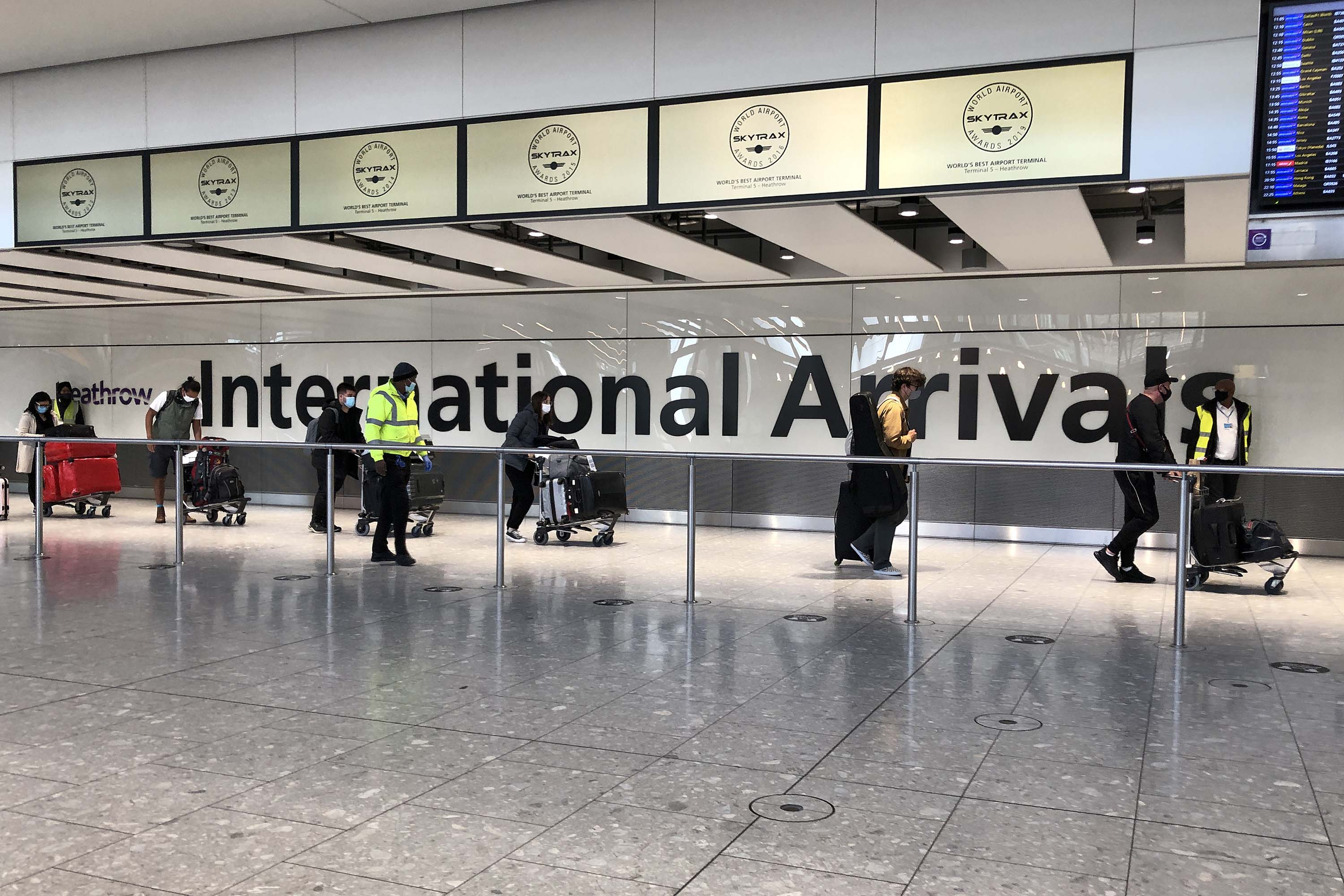 Passengers are escorted through an arrivals area towards buses destined for quarantine hotels, after landing at Heathrow airport in London, on April 23, as travel restrictions remain in place.