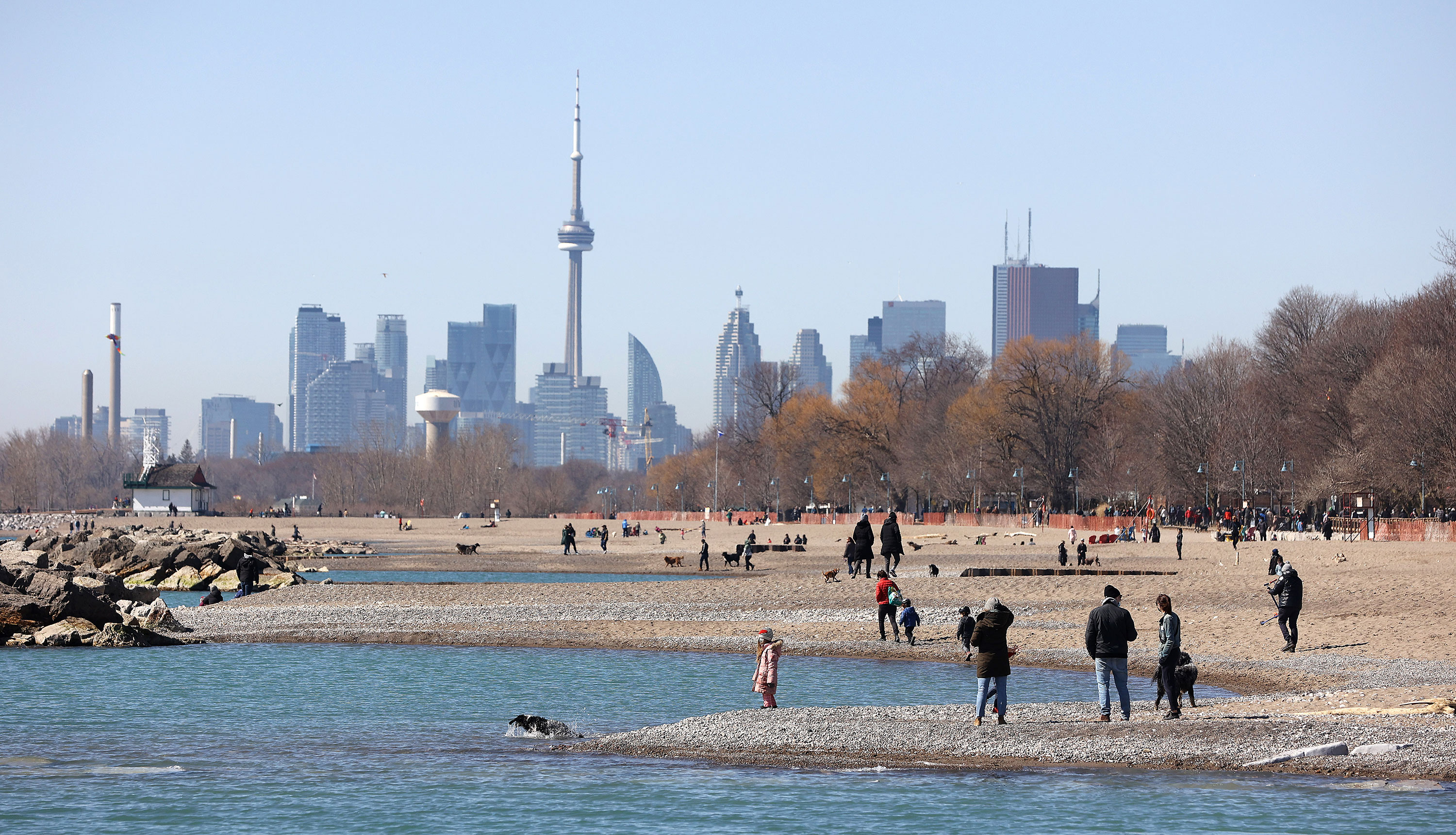 People are seen on a beach near Toronto on March 21.