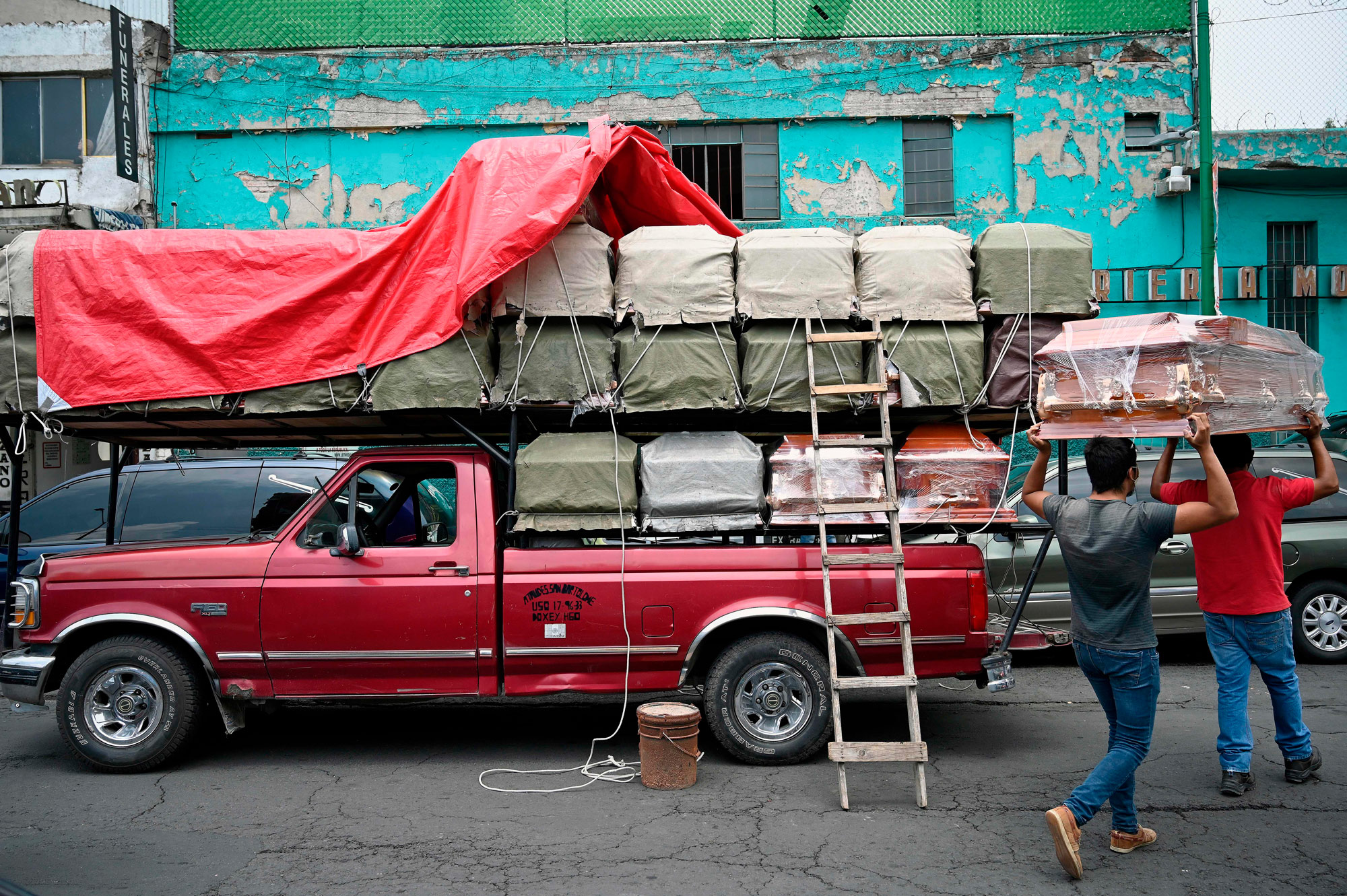 Workers unload coffins from a truck outside a funeral home in Mexico City on August 20.