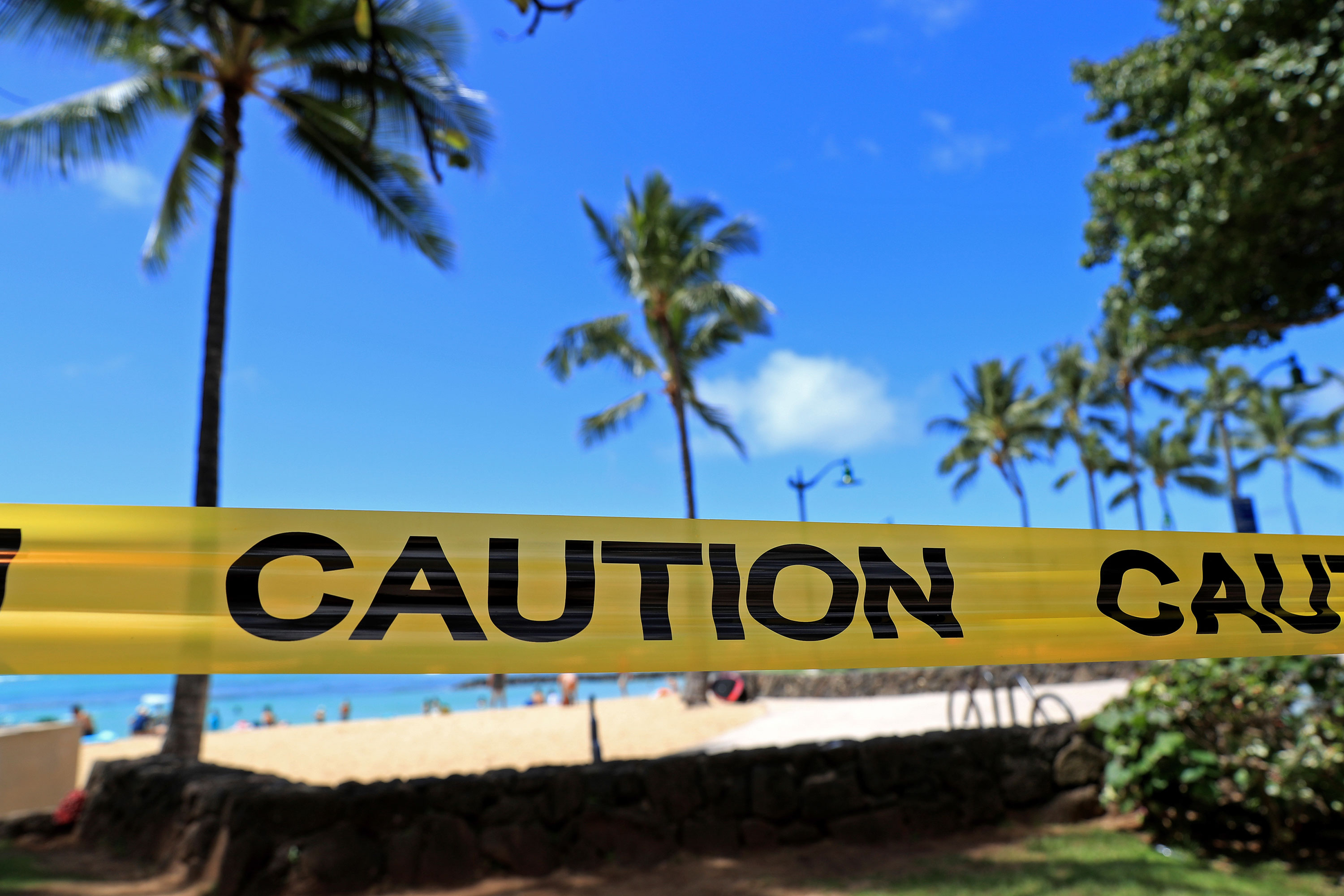 Yellow caution tape is wrapped across an area of Waikiki, after all public parks and recreation areas were closed on March 20 in Honolulu.