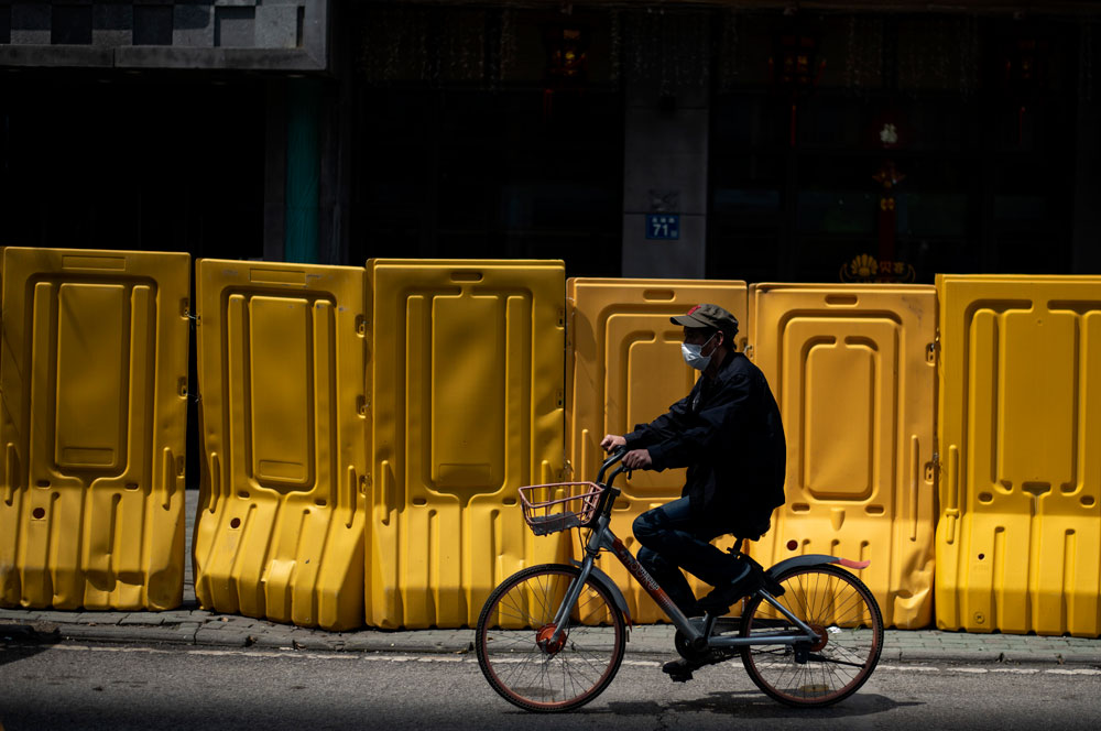 A face mask-clad cyclist rides alongside a barricade separating a residential compound in Wuhan, in China's central Hubei province, on April 6, after some restrictions amid the coronavirus pandemic were eased in the city.