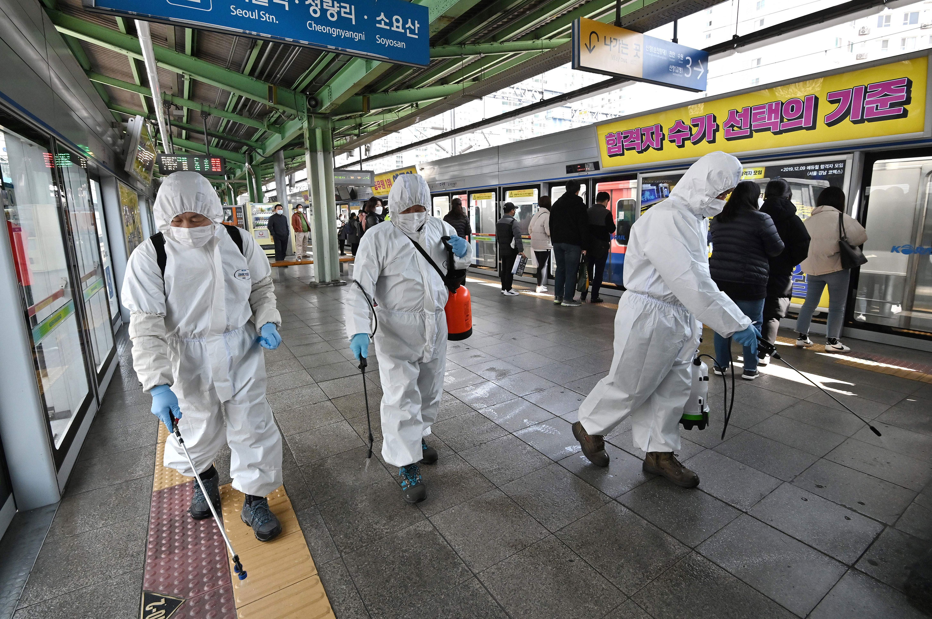 Workers spray disinfectant at a subway station in Seoul on March 13.