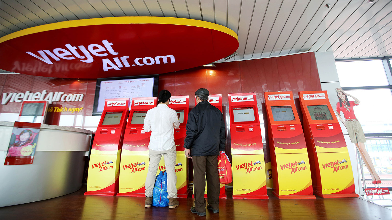 In this 2017 file photo, passengers use an automated check-in machine for VietJet Air at Noi Bai International Airport in Hanoi, Vietnam.