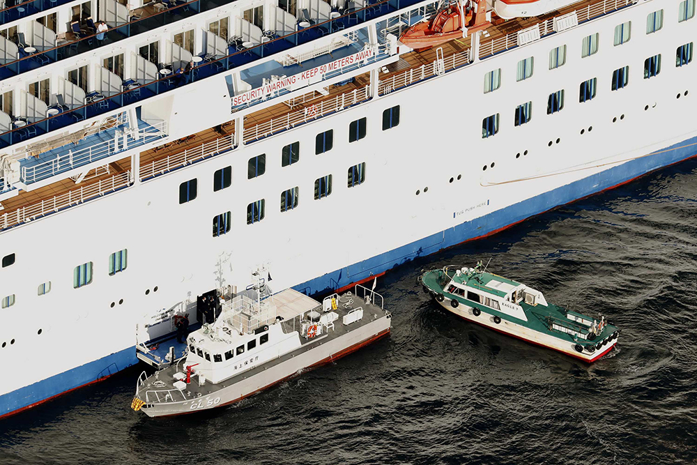 A Japan Coast Guard' patrol boat, left, is brought alongside the cruise ship Diamond Princess to take passengers tested positive for coronavirus to hospitals off Yokohama on Wednesday, February 5.