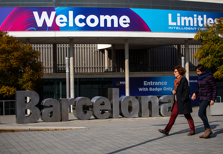 People walk past posters announcing the Mobile World Congress 2020 in a conference venue in Barcelona, Spain, Tuesday, February 11.  The organizer of the event announced that it would be cancelled in a segment on Wednesday.