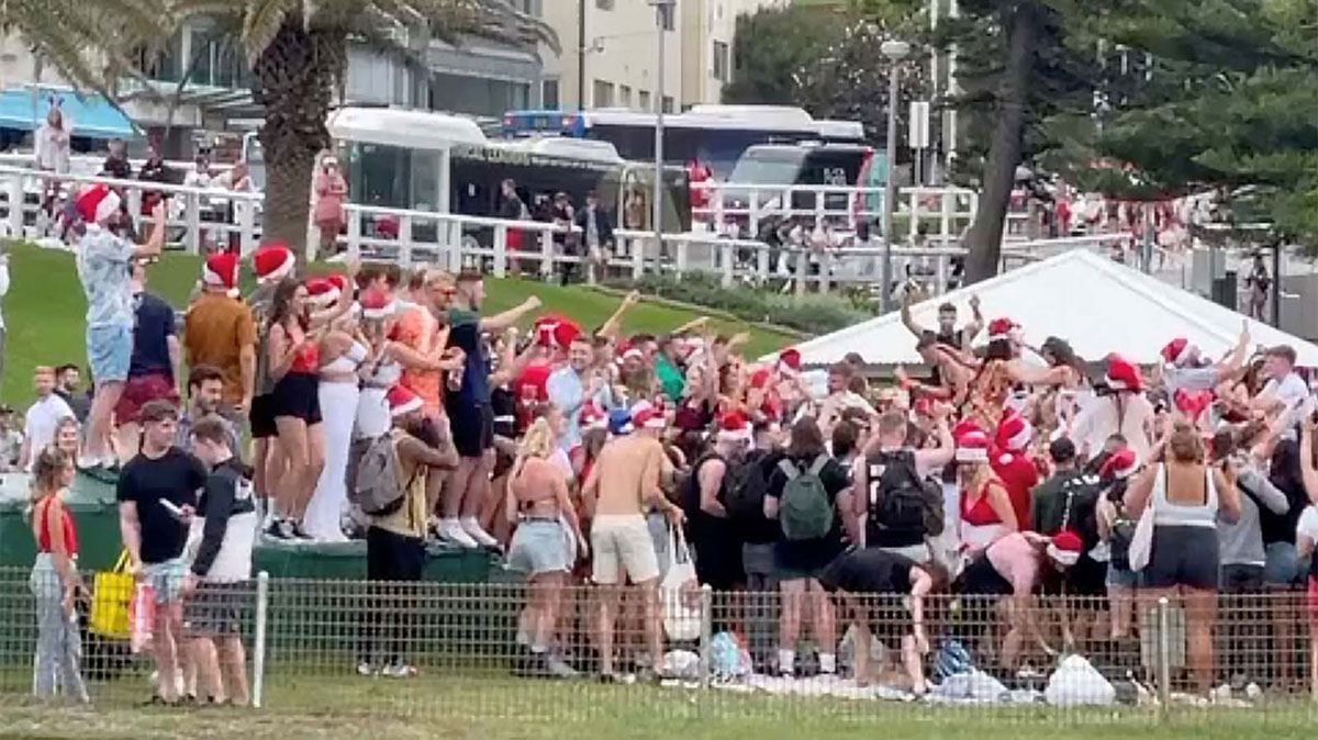 In this still image taken from a social media video, people wearing Santa hats gather at Bronte Beach, in Sydney, Australia, amid the coronavirus outbreak on December 25.