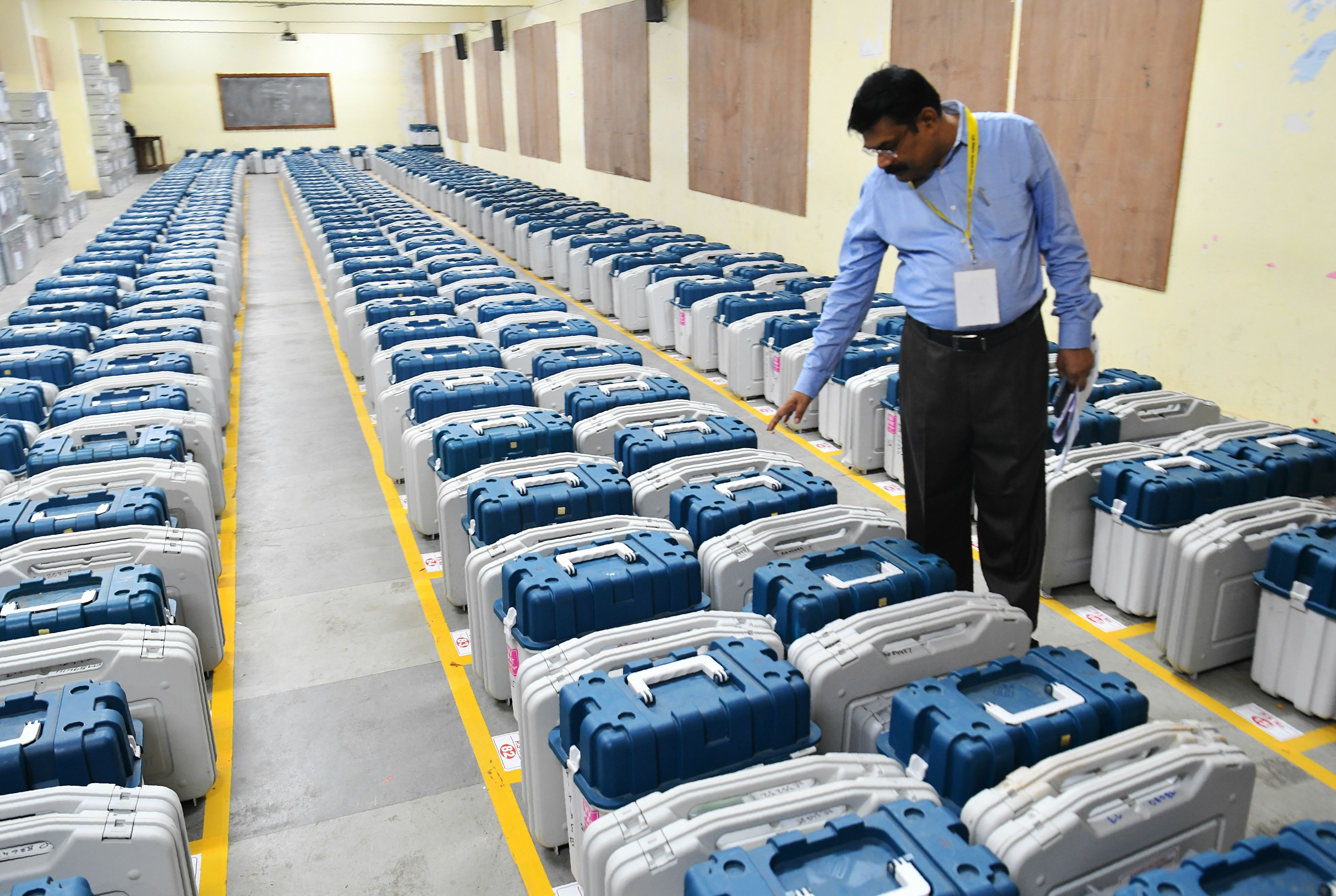 A government official inspects Electronic Voting Machines (EVMs) stored inside the strong room at a polling material and voting machine distribution centre in Bangalore on April 17, 2019.