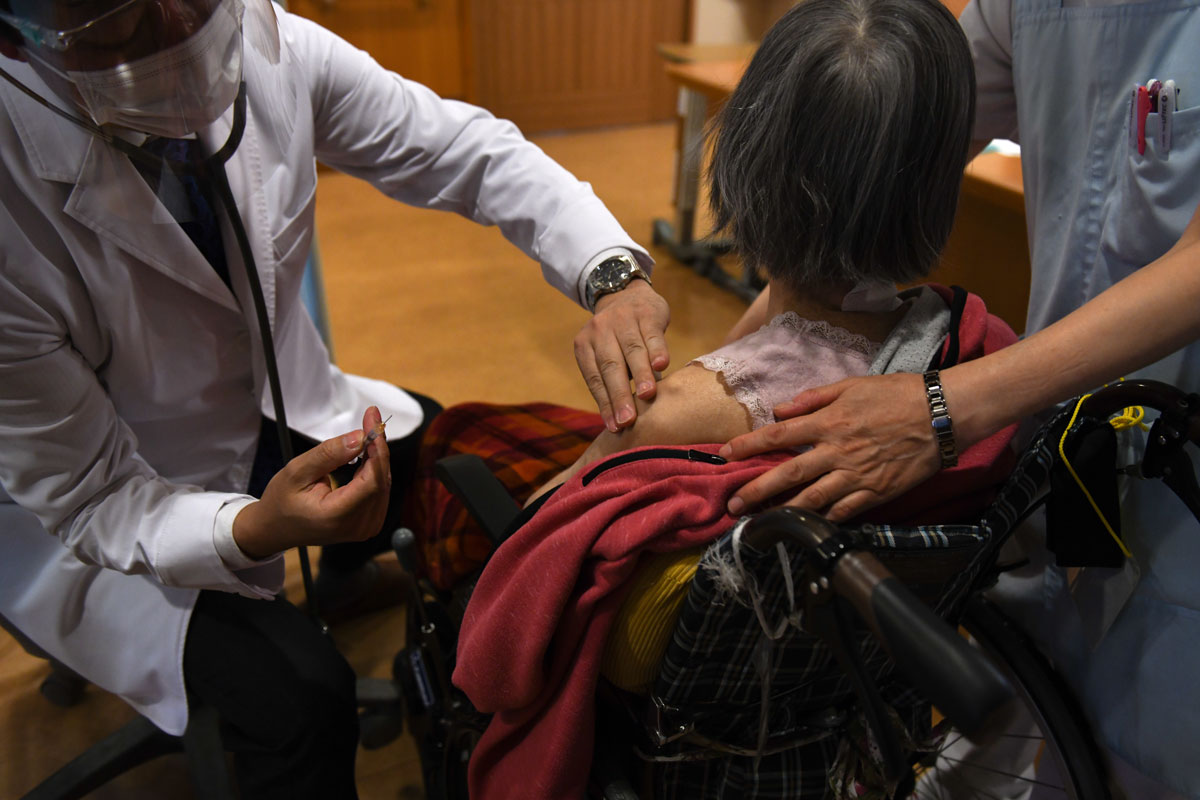 A doctor administers a dose of the Pfizer-BioNTech Covid-19 vaccine at a nursing home in Kanagawa prefecture, Japan, on April 12.