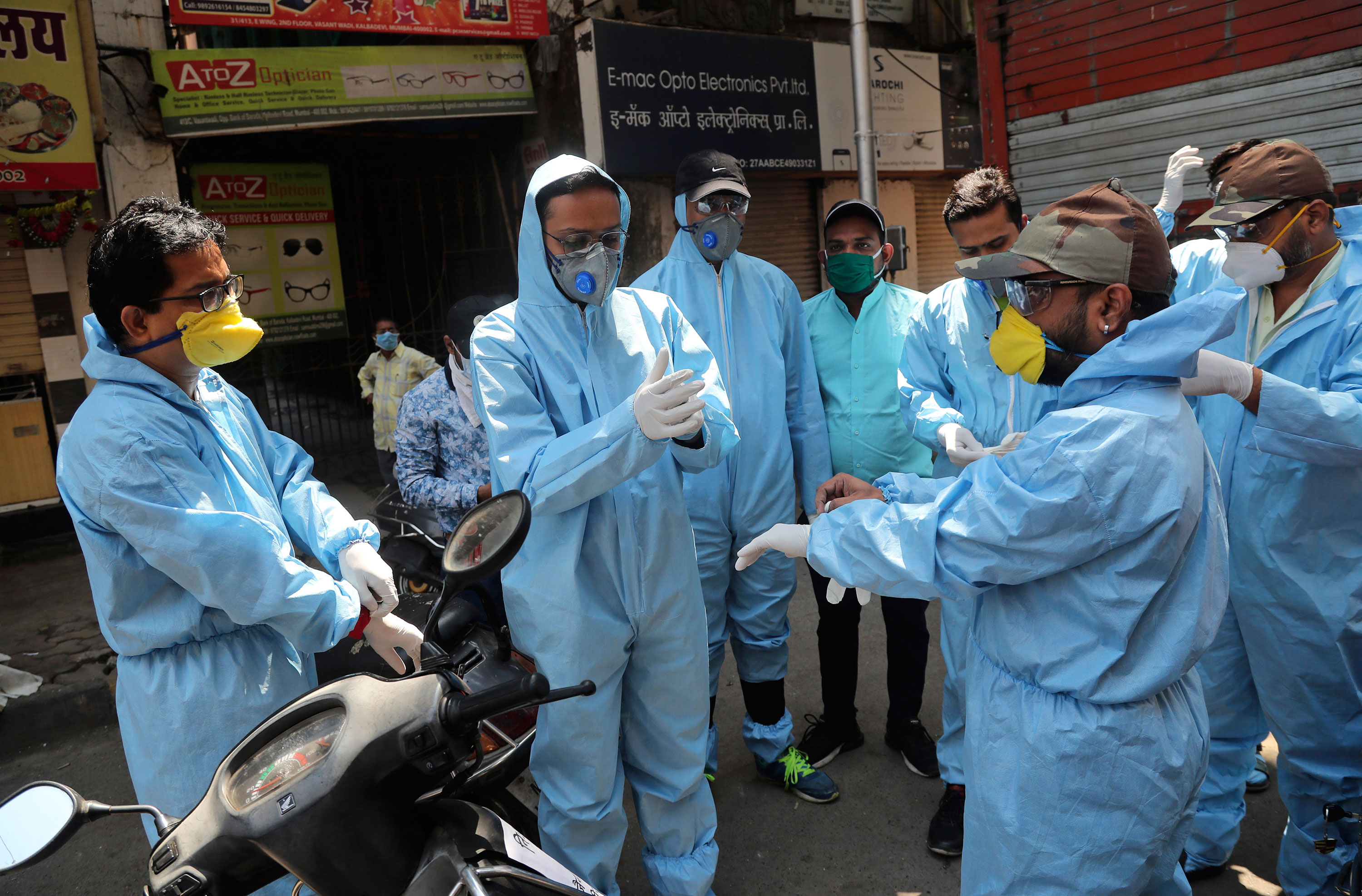 Members of a volunteer organization wear protective gear before distributing food to people in Mumbai, India, on March 29.