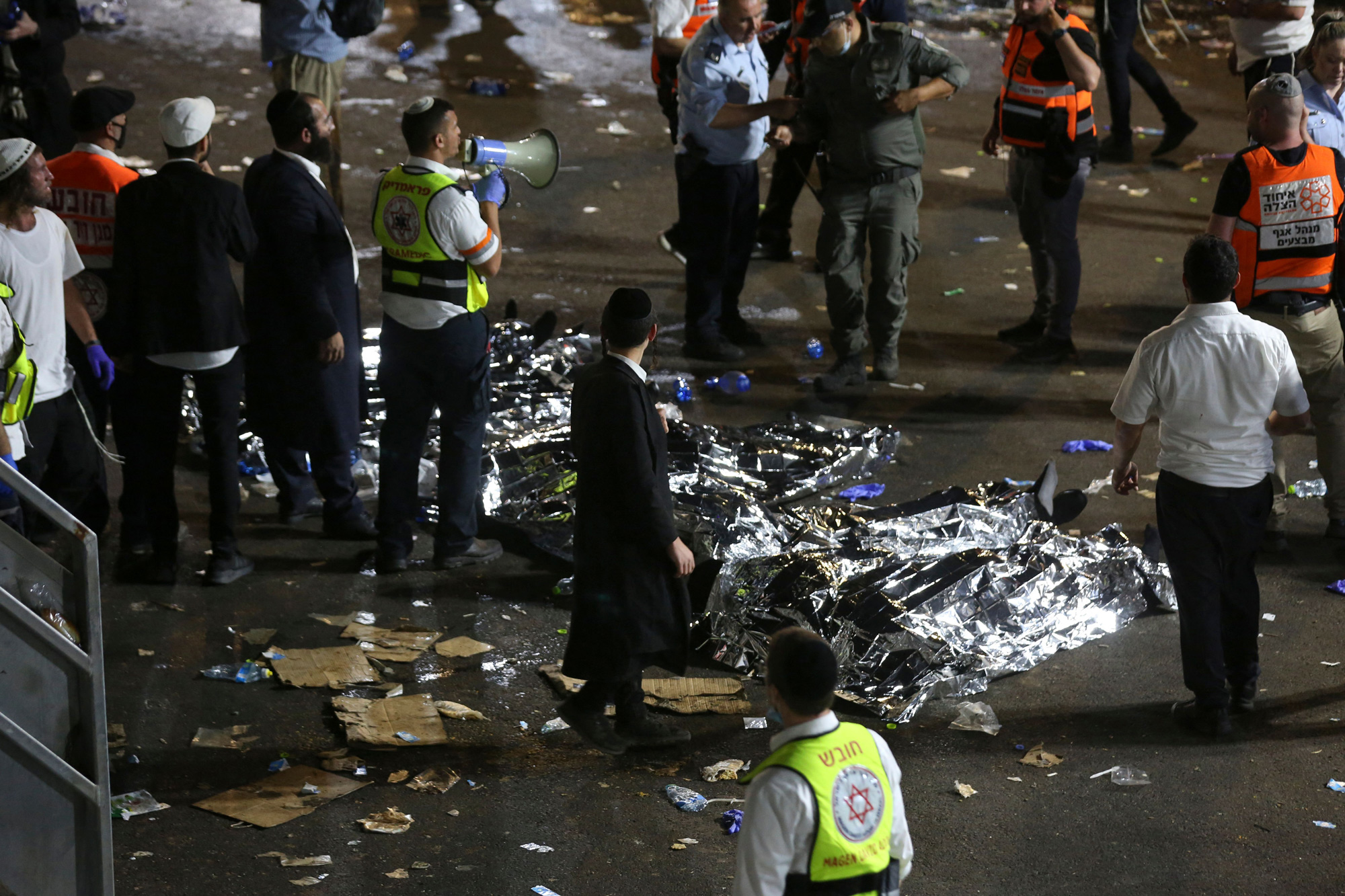 Ultra-Orthodox Jewish men stand next to covered bodies after dozens of people were killed and others injured during Lag Ba'omer celebrations at Mount Meron on April 30.