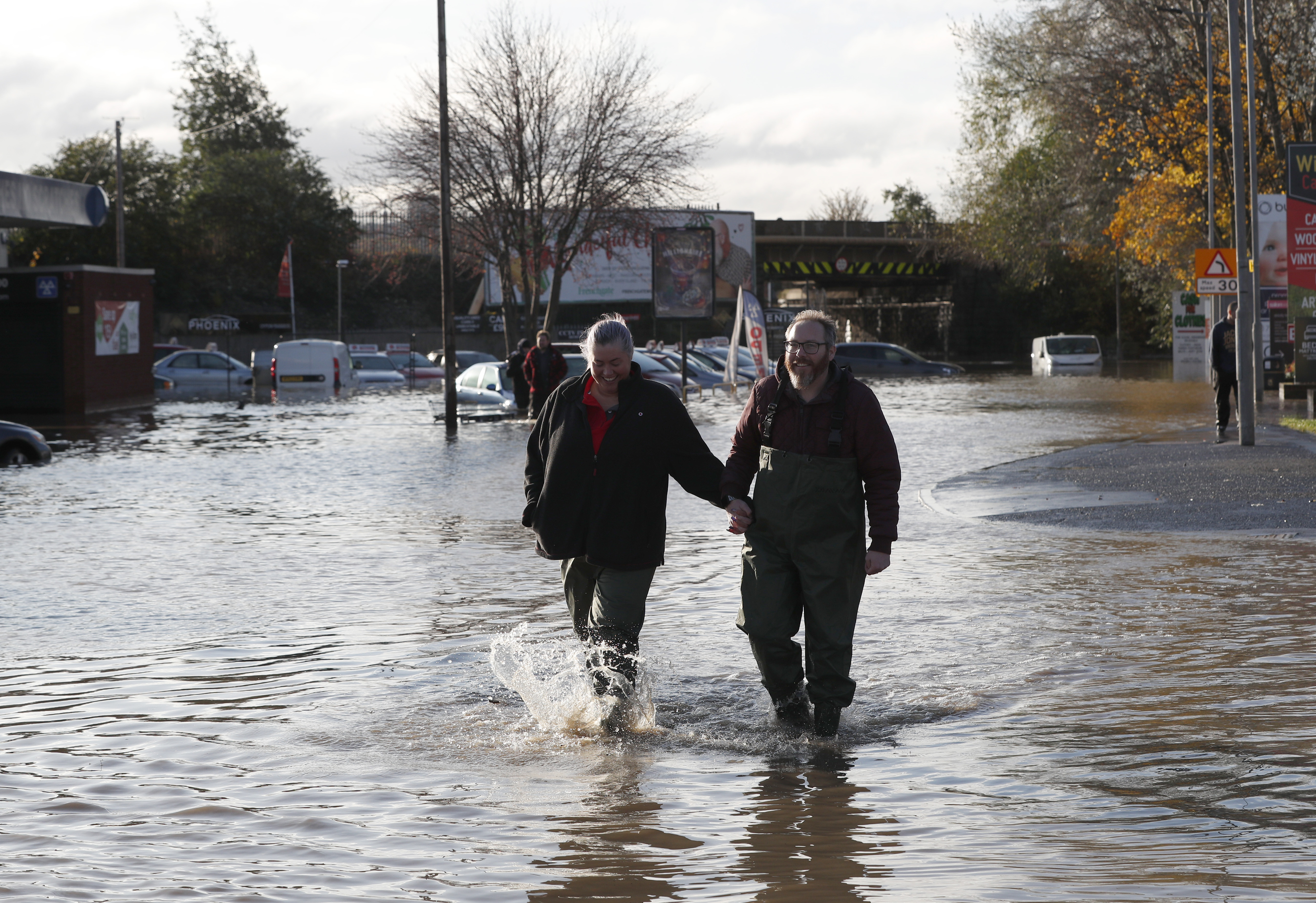 A couple wade through flood waters after the River Don burst its banks.