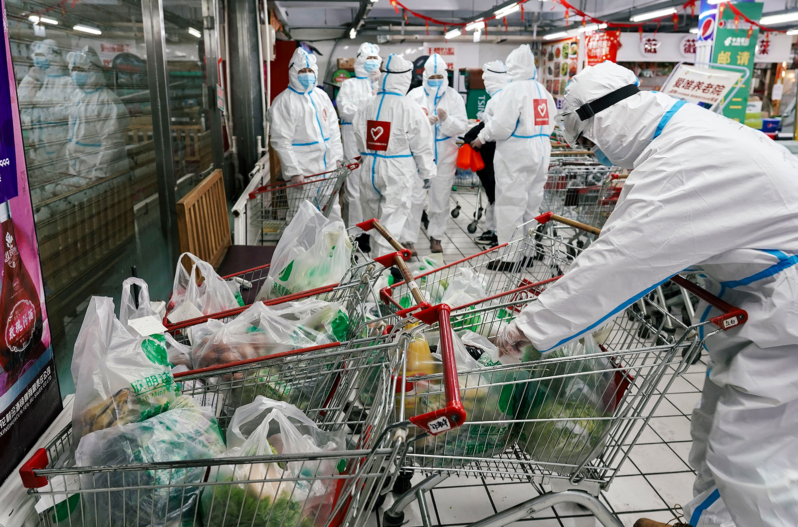 Volunteers check orders of daily necessity goods at a supermarket according to wish lists of residents in quarantine in Tonghua, China, on January 24.