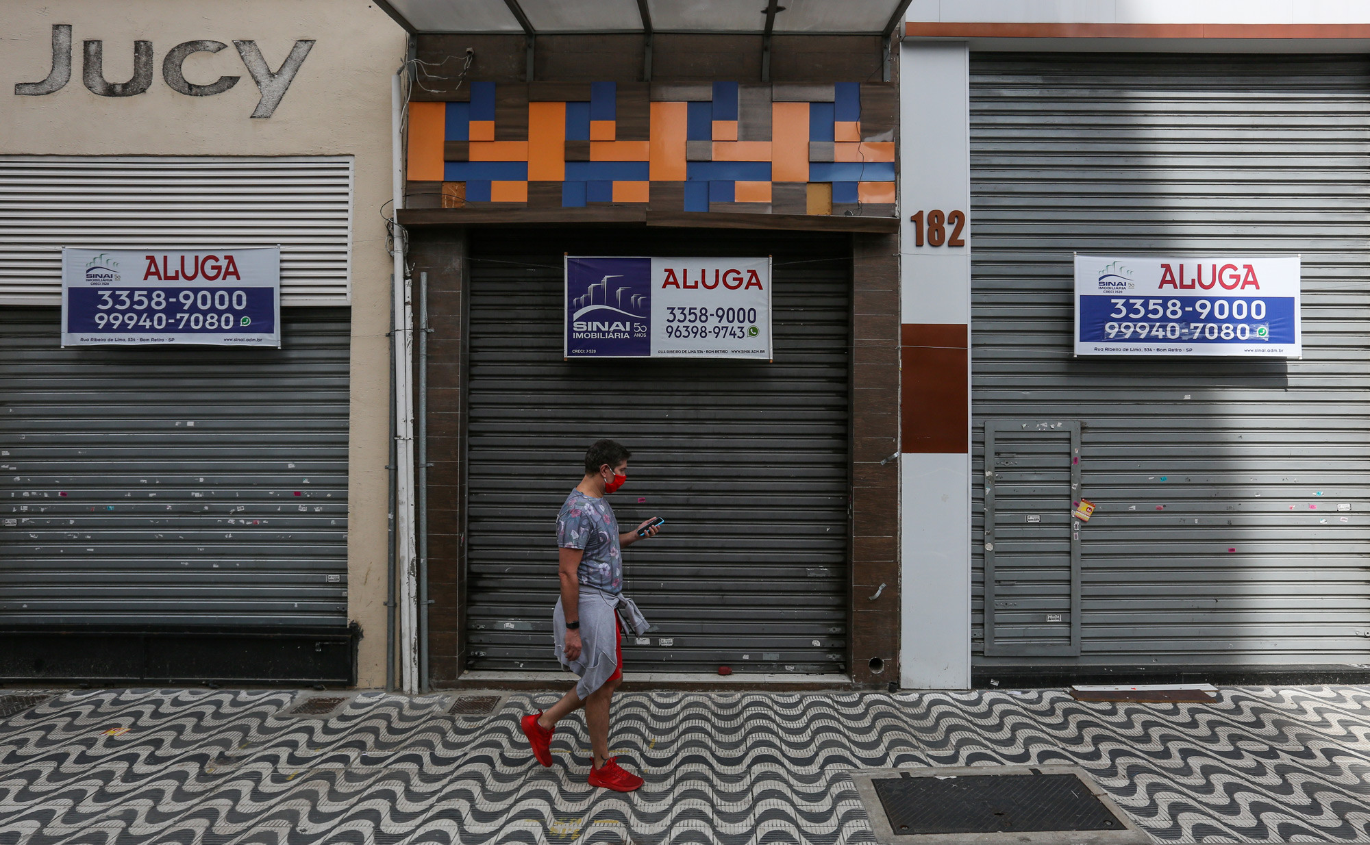 A man walks in front of a shuttered shop on June 29 in Sao Paulo, Brazil.
