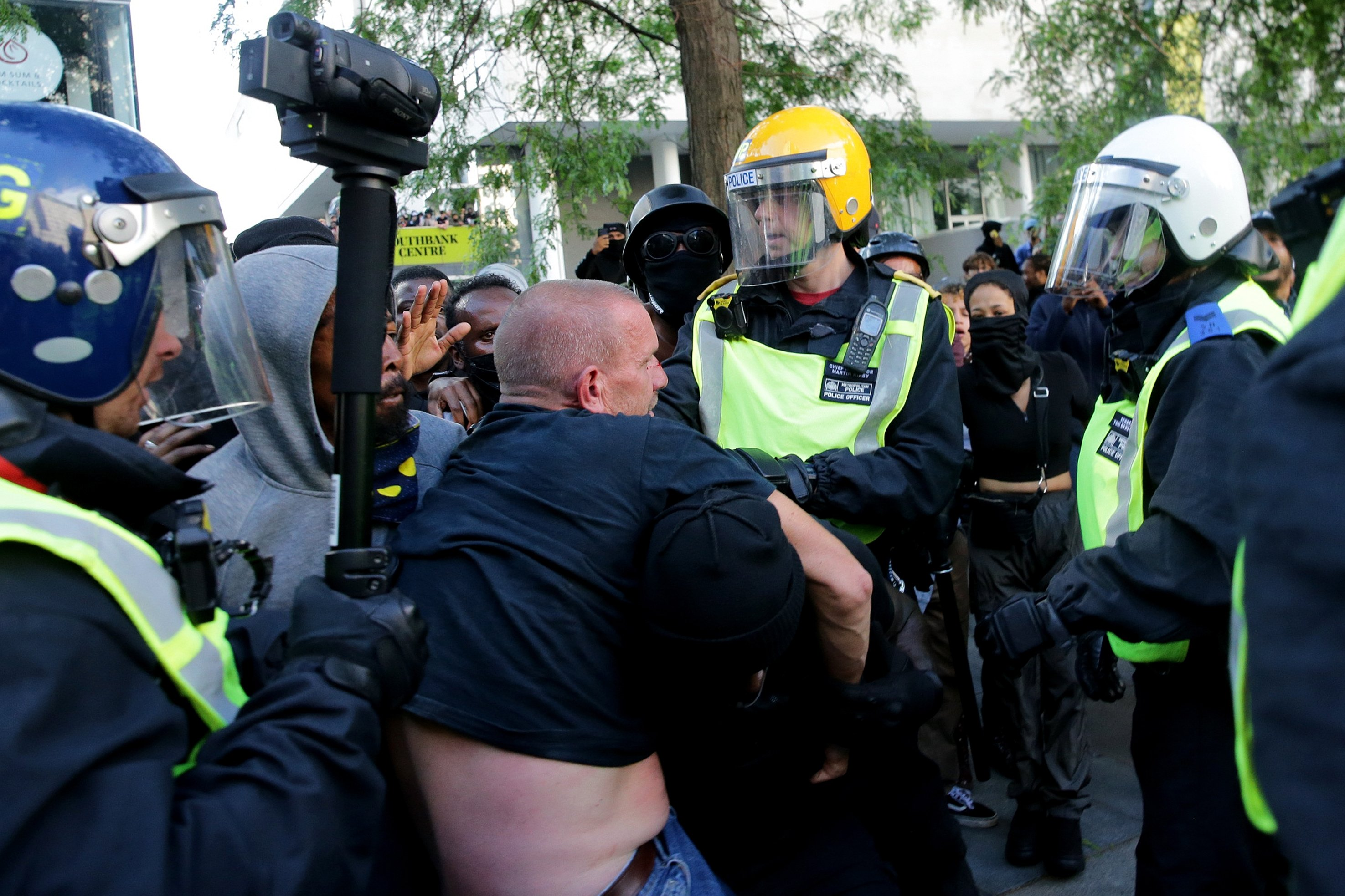 A group of men carry an injured man away after he was allegedly attacked by some of the crowd of protesters, as police try to intervene on the Southbank near Waterloo station in London on June 13, 2020.