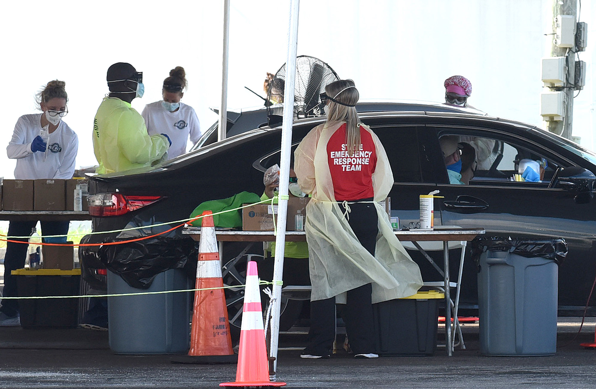Health care workers perform Covid-19 testing at a drive-through site at Eastern Florida State College on October 9, in Palm Bay, Florida.