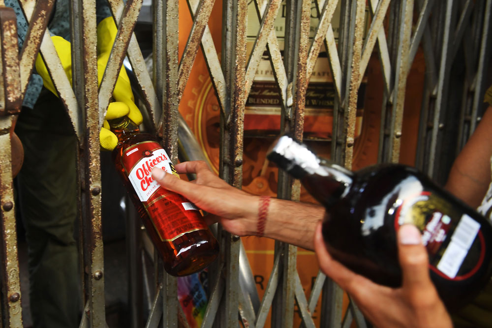 A liquor shop worker wearing gloves gives bottles of alcohol to a customer through the shutters of the shop after the government eased a nationwide lockdown imposed as a preventive measure against the coronavirus, in Kolkata on May 4.