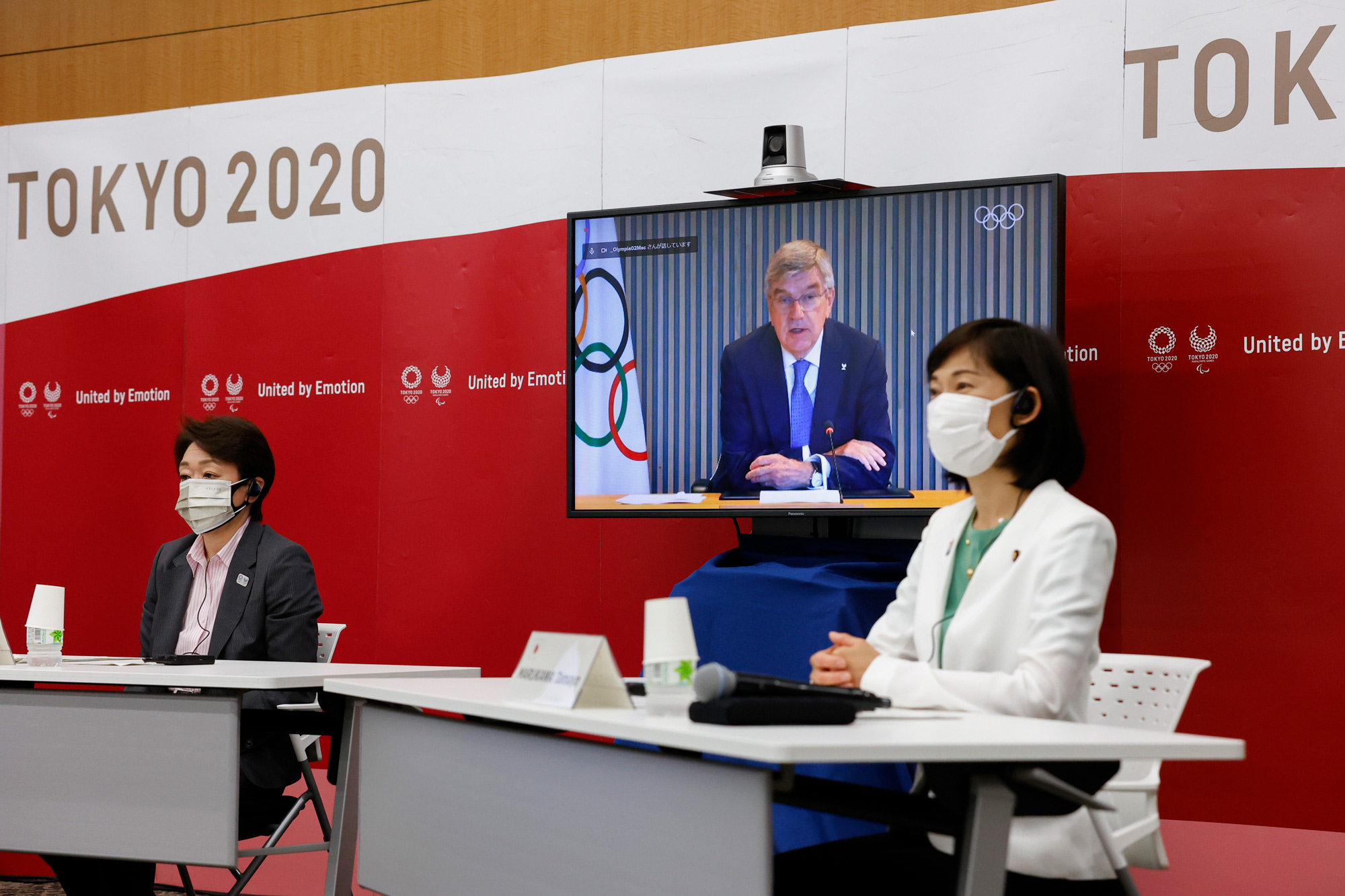 Tokyo 2020 President Seiko Hashimoto, left, Japanese Olympic Minister Tamayo Marukawa, right, and IOC President Thomas Bach, on a screen, attend a five-party online meeting at Harumi Island Triton Square Tower Y in Tokyo on June 21.