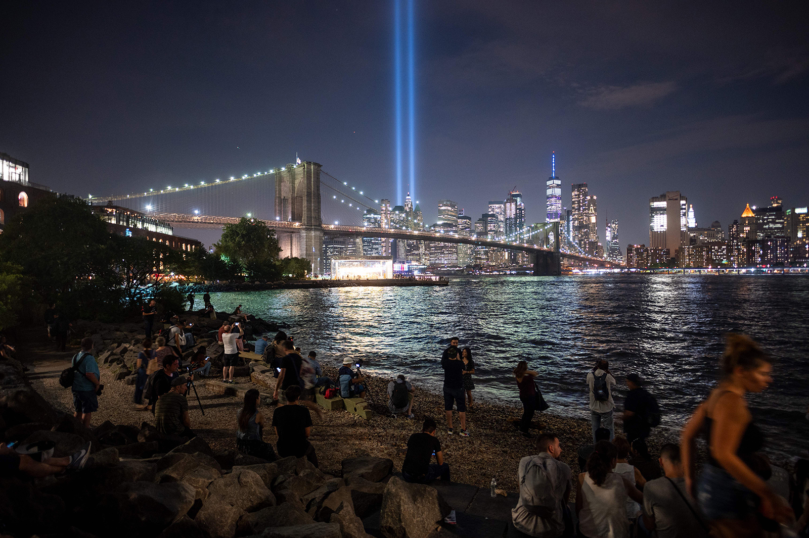 People on the shore watch The Tribute in Light shining into the sky over Manhattan's skyline on September 11, 2019.
