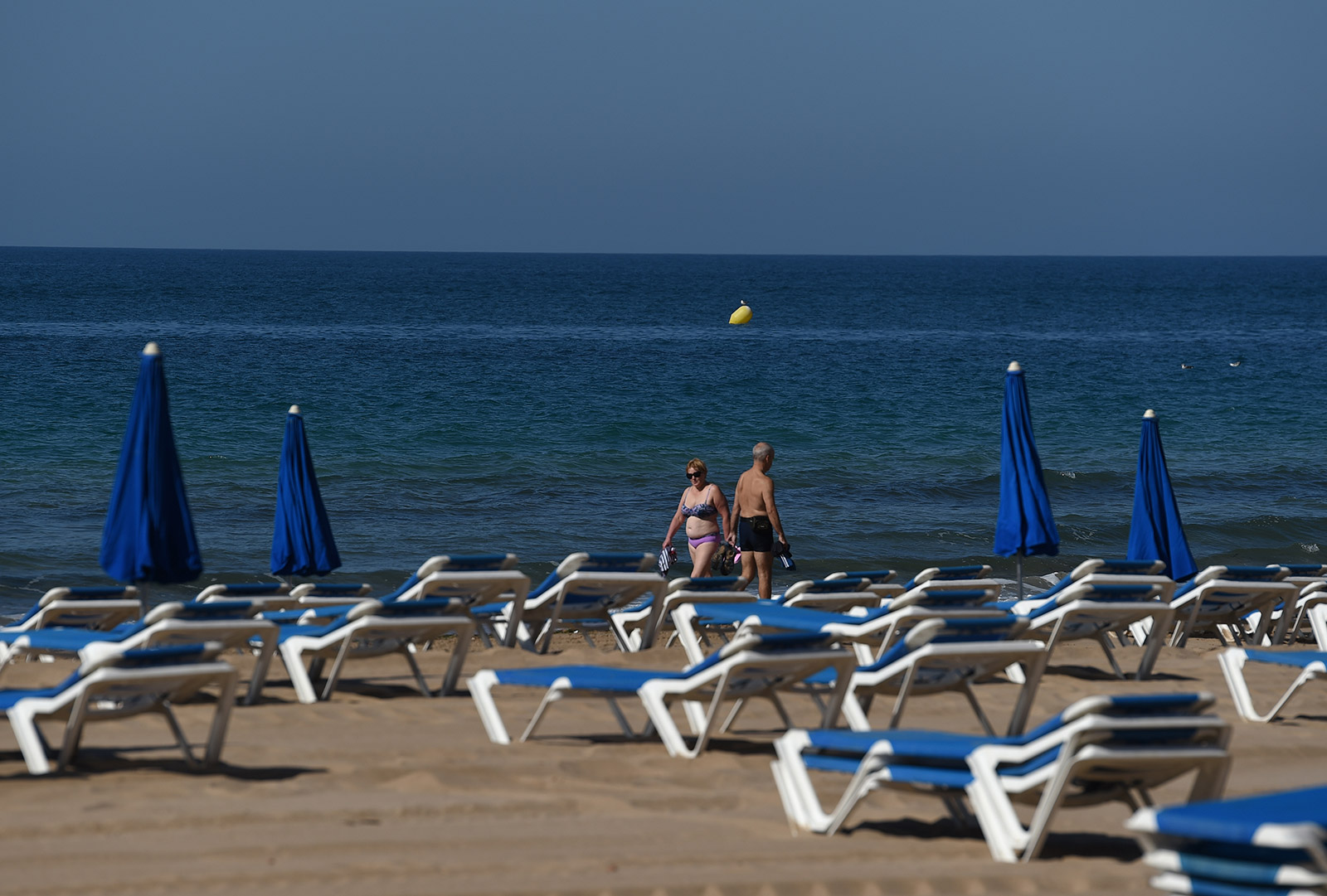 People walk past empty chairs at the beach Benidorm, Spain, on June 15.
