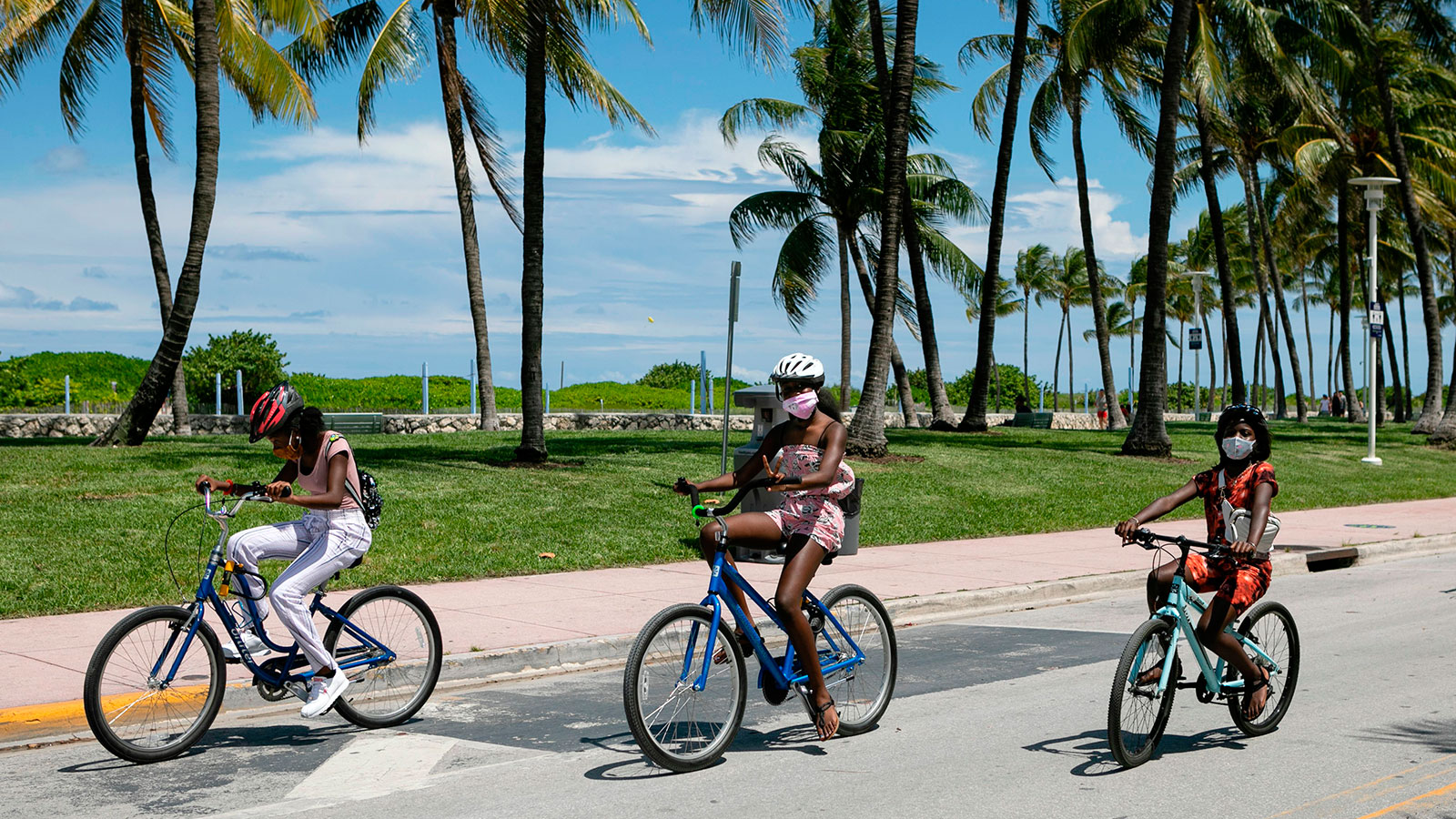 People wearing facemasks ride bicycles on Ocean Drive in Miami Beach, Florida on June 16.