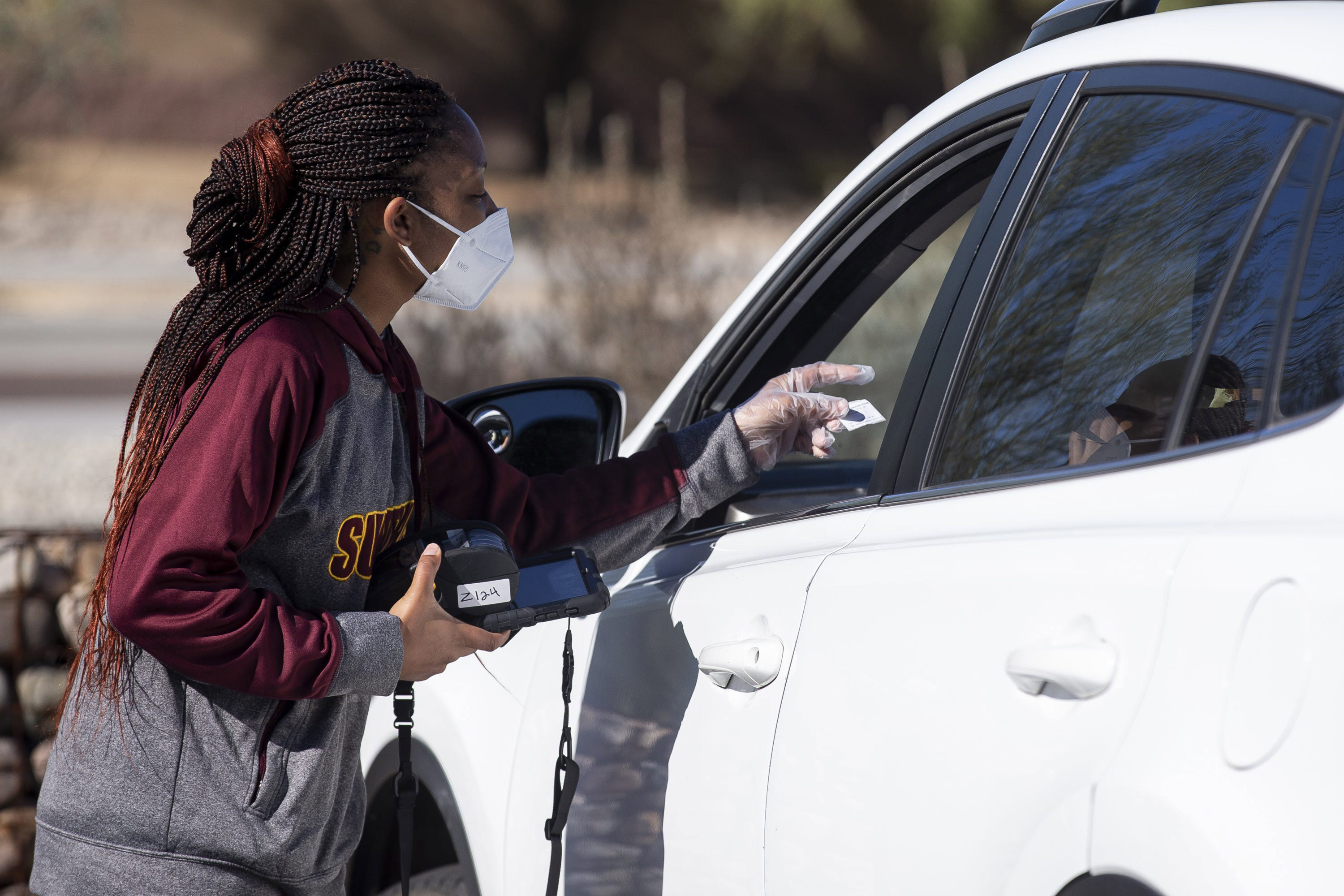 Latajah Byron, a medical assistant at Embry Women's Health, registers a person at a COVID-19 testing site on December 2 in Peoria, Arizona.