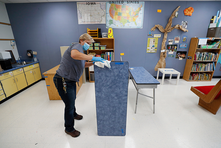 Des Moines Public Schools custodian Cynthia Adams cleans a desk in a classroom at Brubaker Elementary School, Wednesday, July 8, in Des Moines, Iowa.