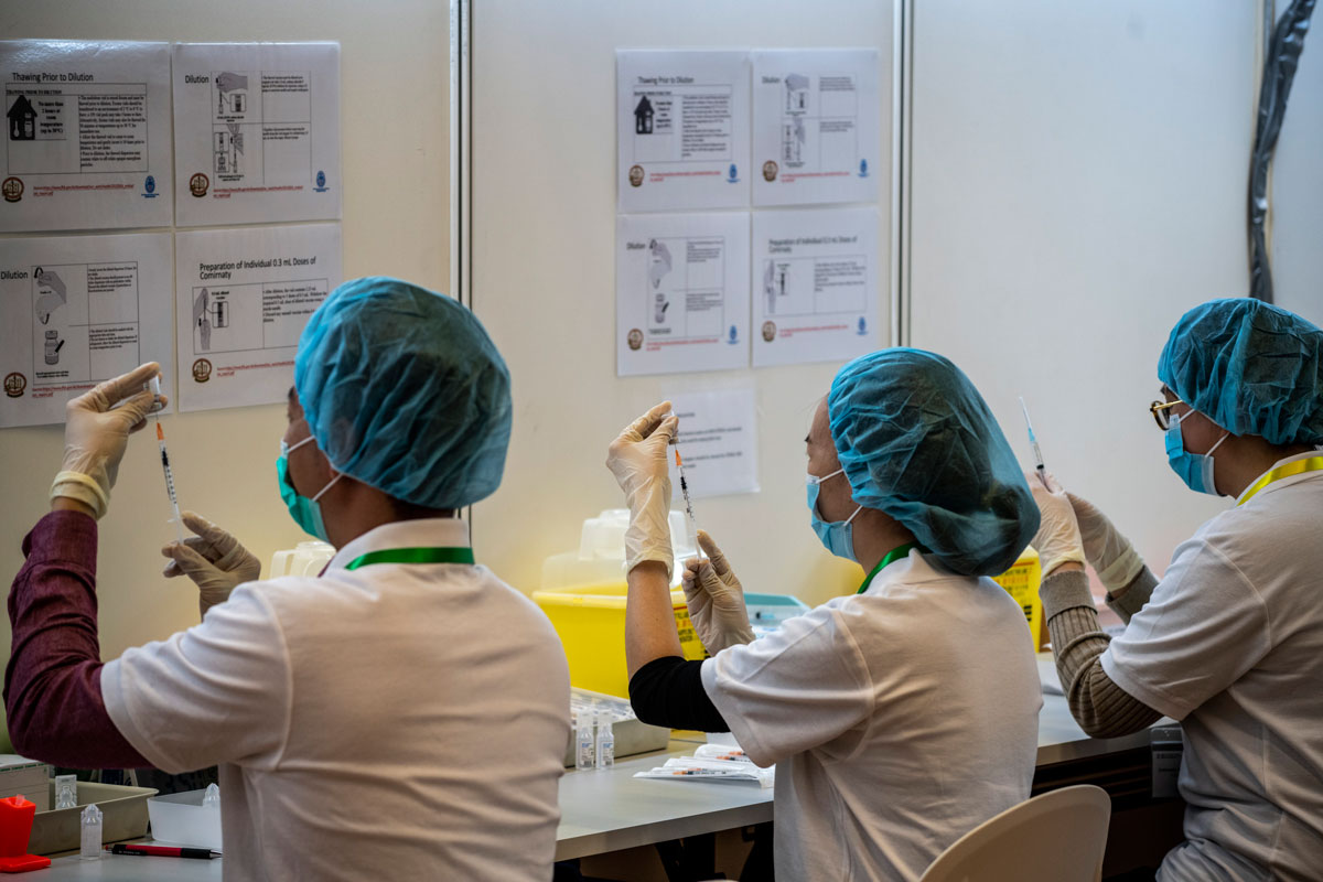 Pharmacists are seen at a vaccination center run by the University of Hong Kong on March 13.