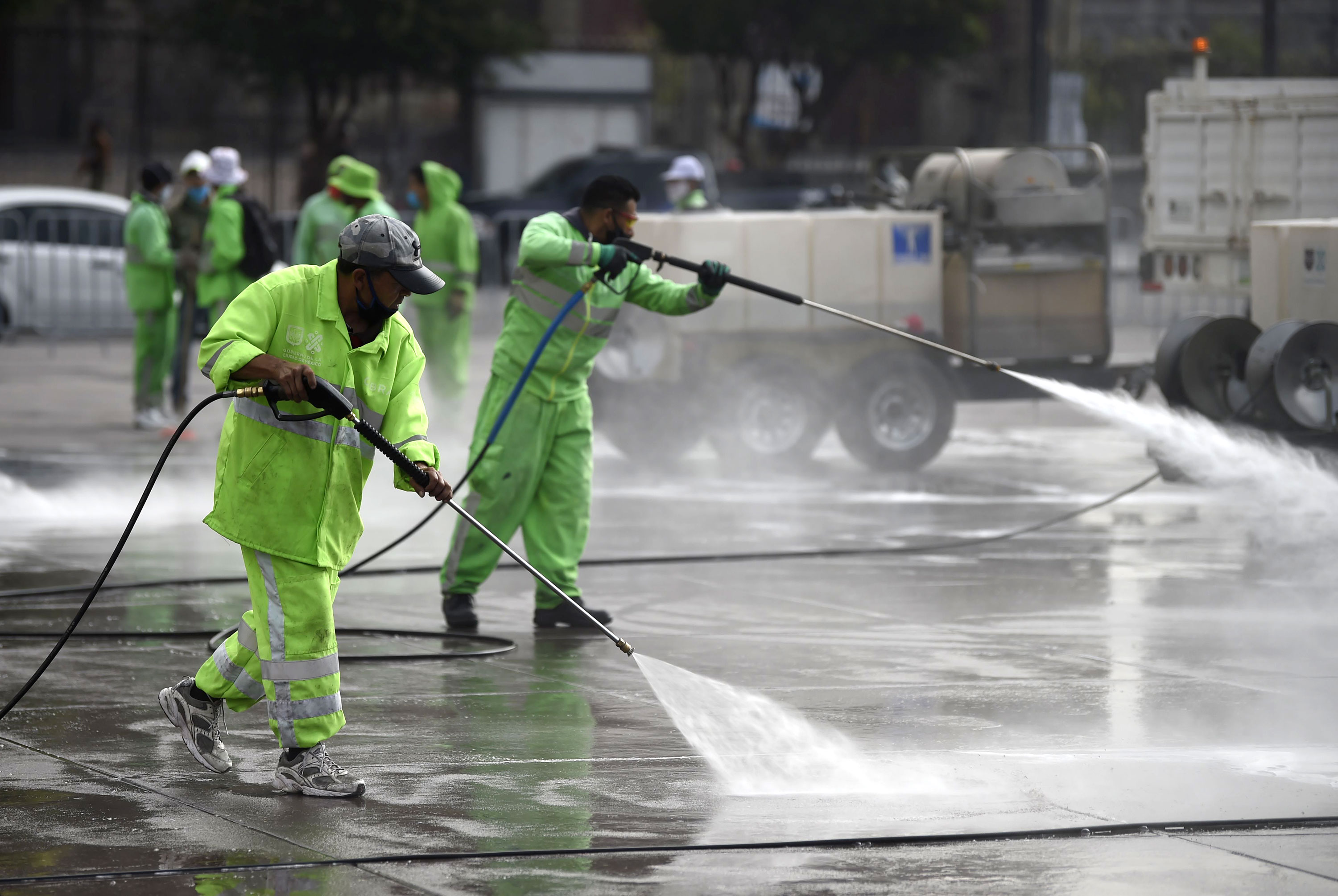 Workers disinfect and clean the Zocalo square in Mexico City on June 29.