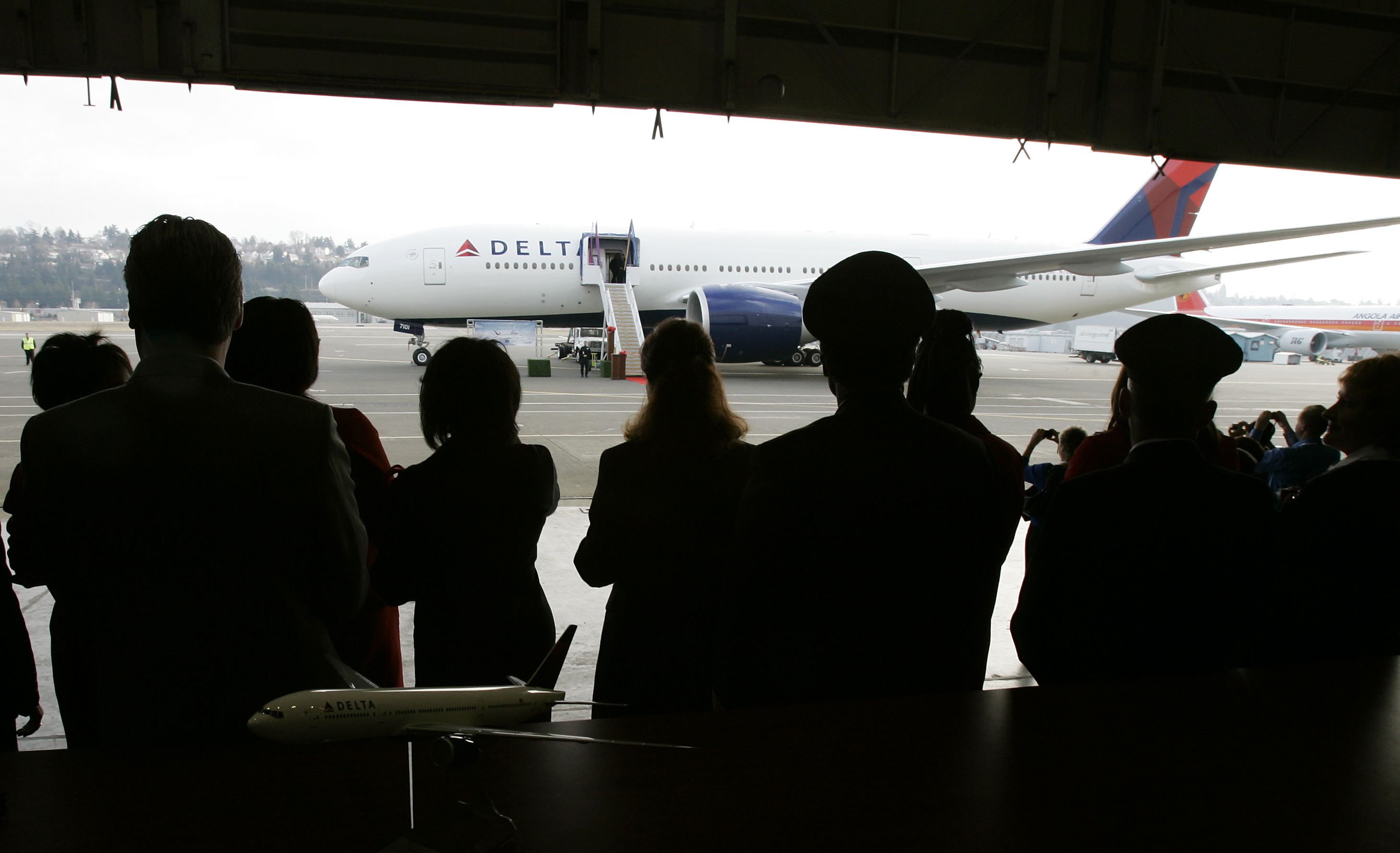 Executives and pilots from Delta Air Lines, Inc. look on at Boeing Field in Seattle as a hangar door opens to reveal the then new Boeing 777-200 LR airplane on February 29, 2008.