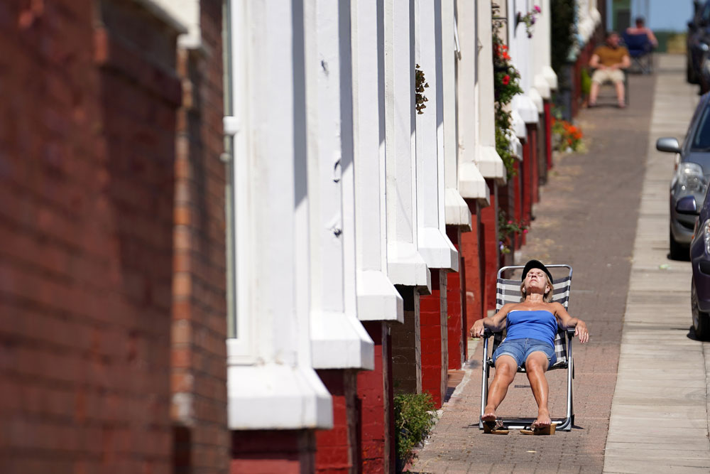 People enjoy the warm and sunny weather relaxing on the pavement outside their homes in the Shorefields area of Liverpool on May 28 in Liverpool.