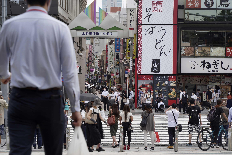 Pedestrian cross a street in Tokyo on Friday, July 30.