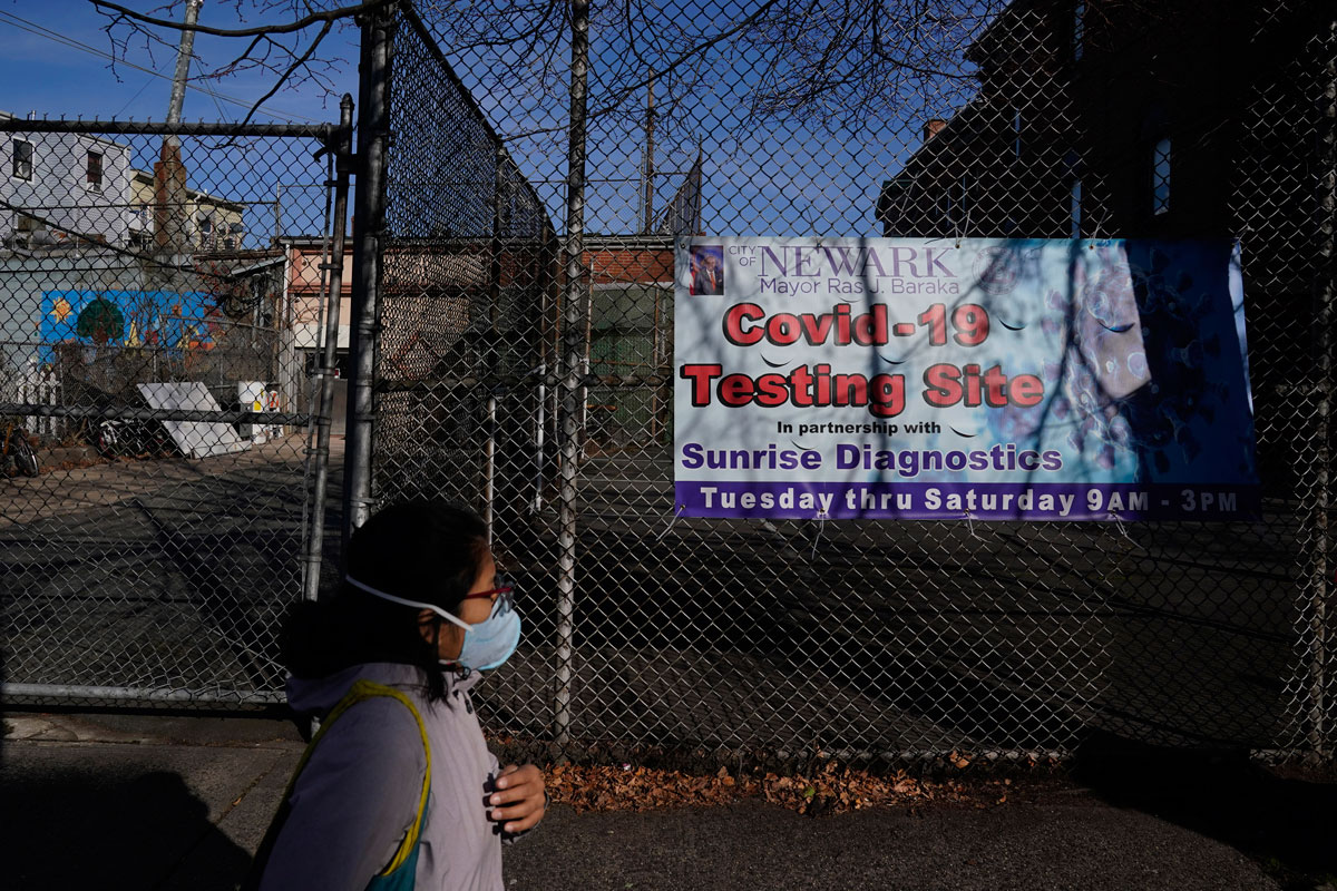 A woman walks past a coronavirus testing site in the Ironbound section of Newark, New Jersey on November 24.