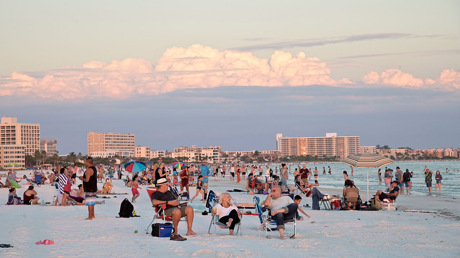 Visitors enjoy Siesta Key Beach as the sun sets over the Gulf of Mexico in Sarasota, Florida on June 17.