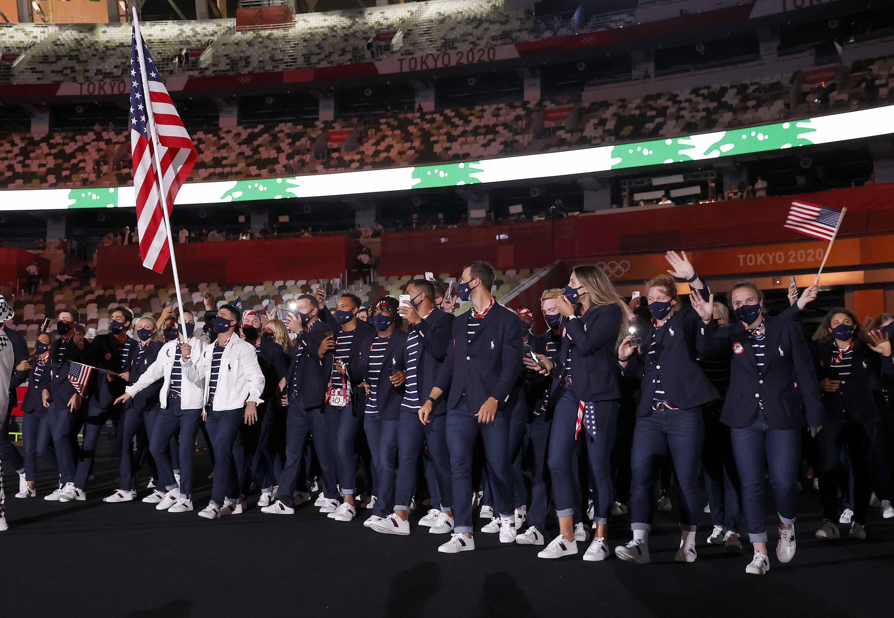 Flag bearers Sue Bird and Eddy Alvares of Team United States lead their team out during the Opening Ceremony.