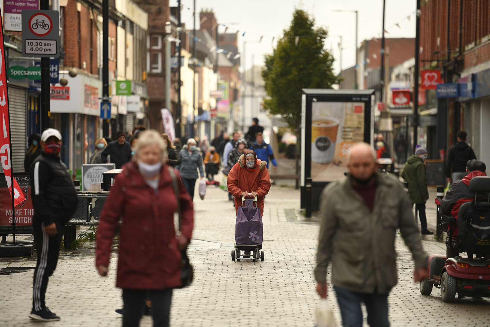People wearing masks because the novel coronavirus pandemic walk in the high street in Leigh, Greater Manchester, northwest England on October 22.
