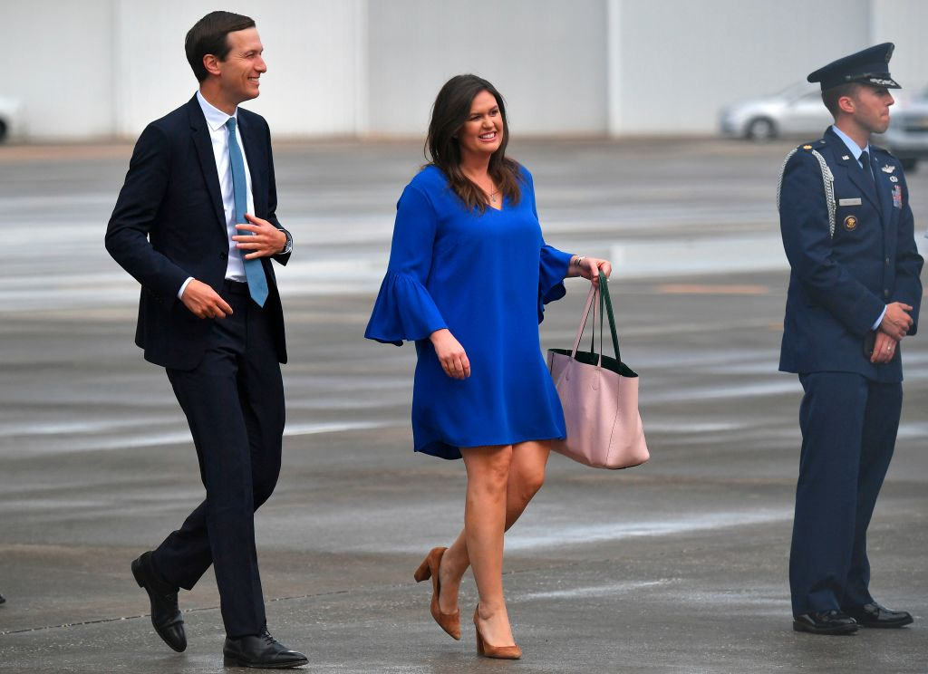 Jared Kushner and White House press secretary Sarah Sanders wait for the arrival of President Trump and first lady Melania Trump at Orlando International Airport on June 18, 2019.