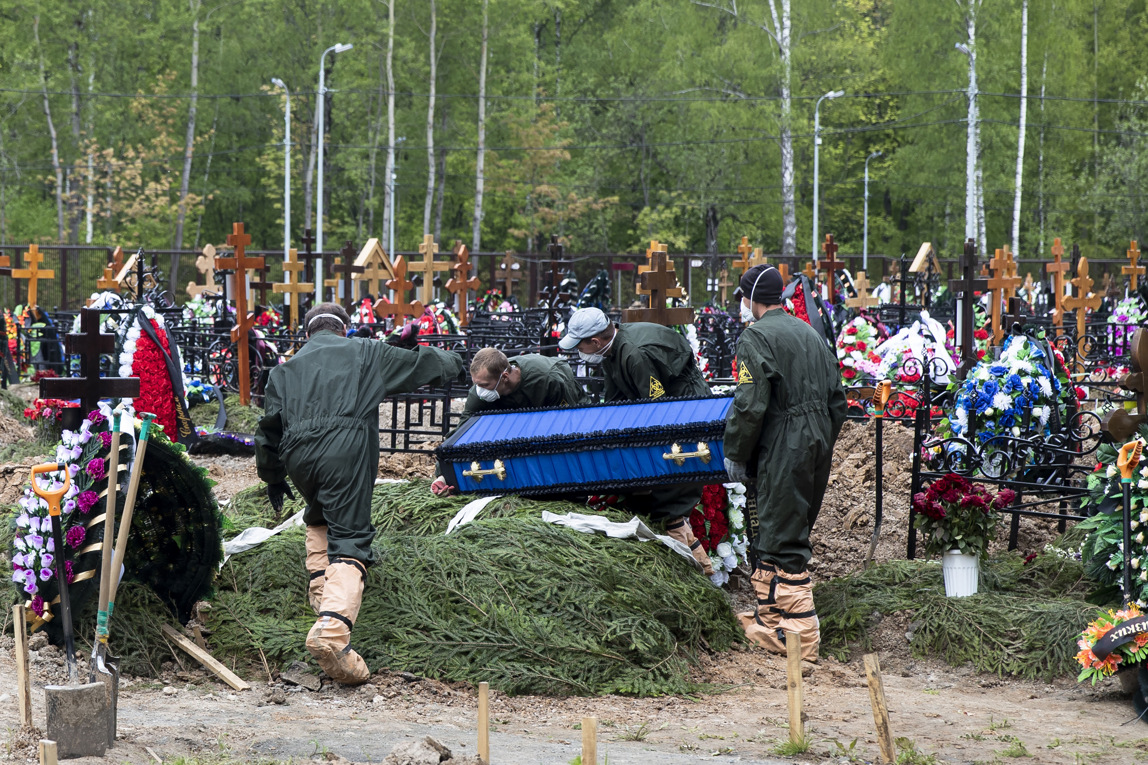 Grave diggers carry the coffin of a Covid-19 patient, in a section of a cemetery reserved for coronavirus victims, outside Moscow on May 26.