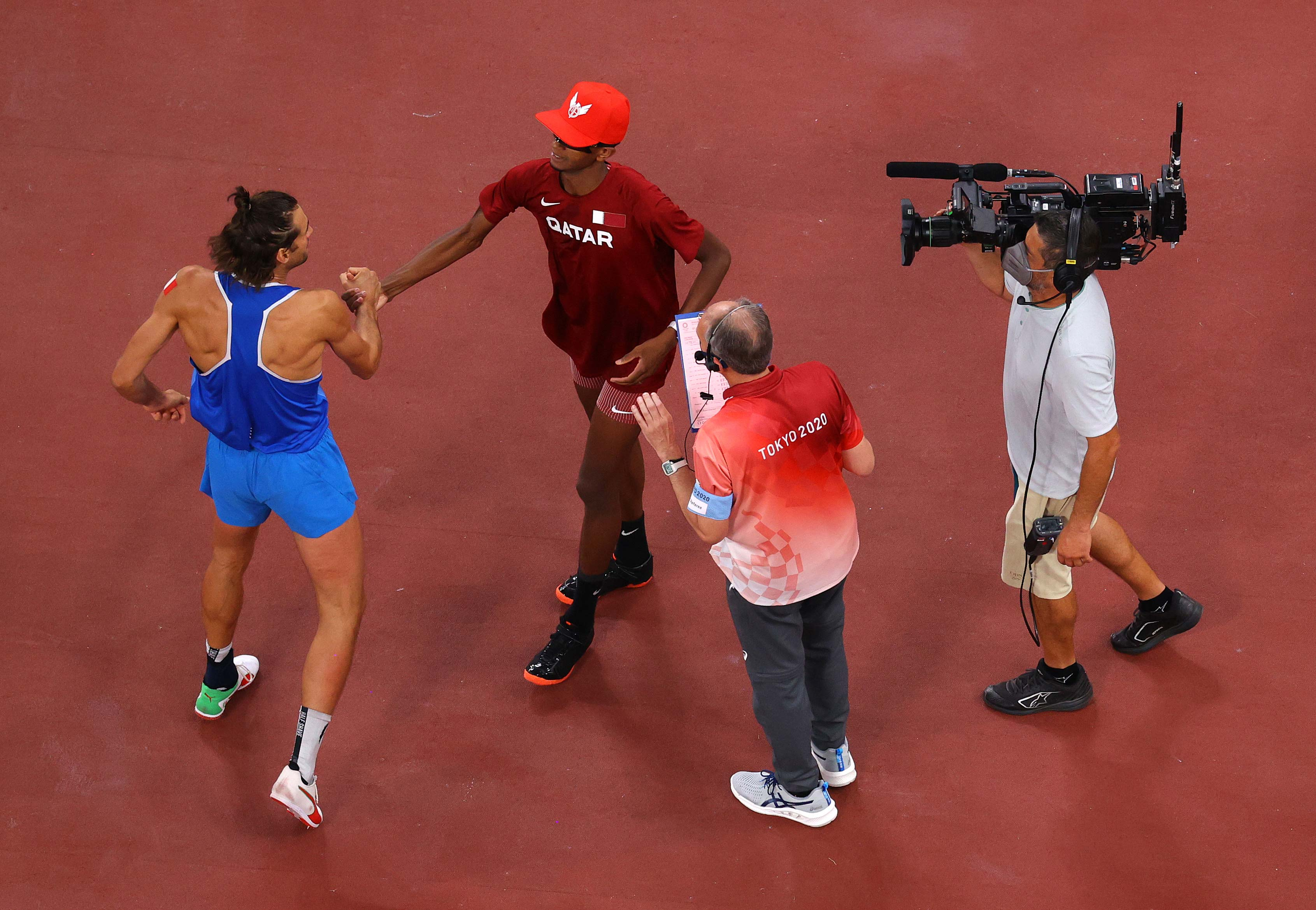 Italy's Gianmarco Tamberi and Qatar's Mutaz Essa Barshim react after winning the gold medal in the high jump on August 01.